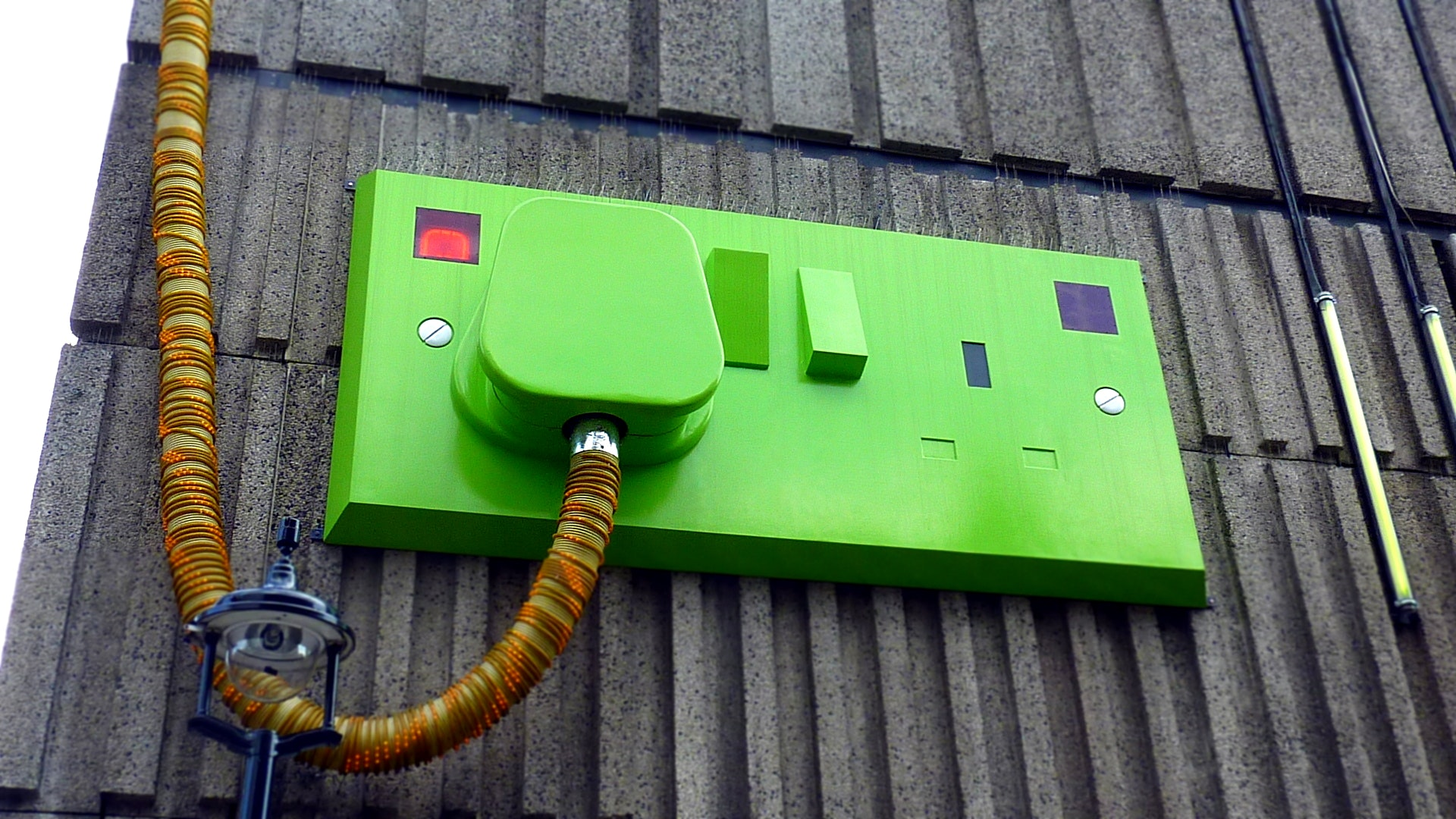 Green rectangular corded machine on grey wall during daytime photo