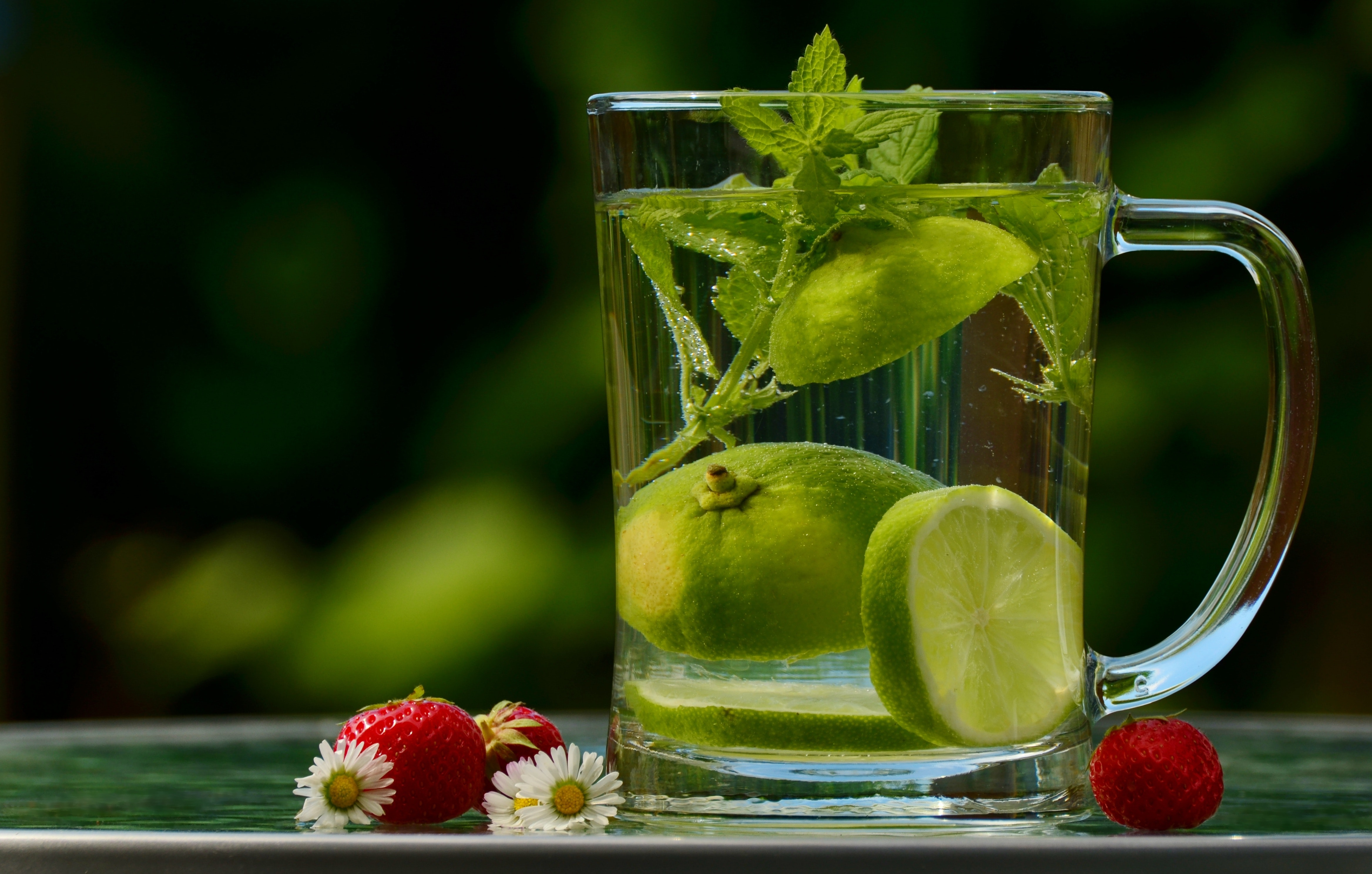 Green round fruit on clear glass mug with water photo