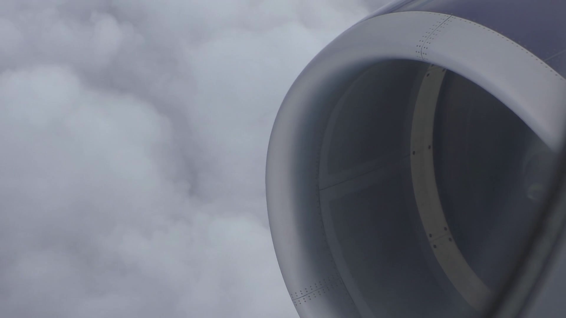 Close up of spinning aircraft engine in flight above grey clouds ...