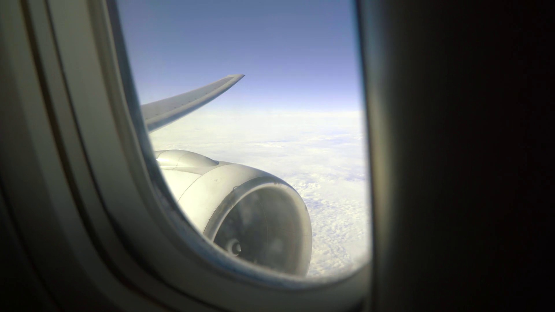 Leaning aircraft passenger window view of airplane turbine above ...