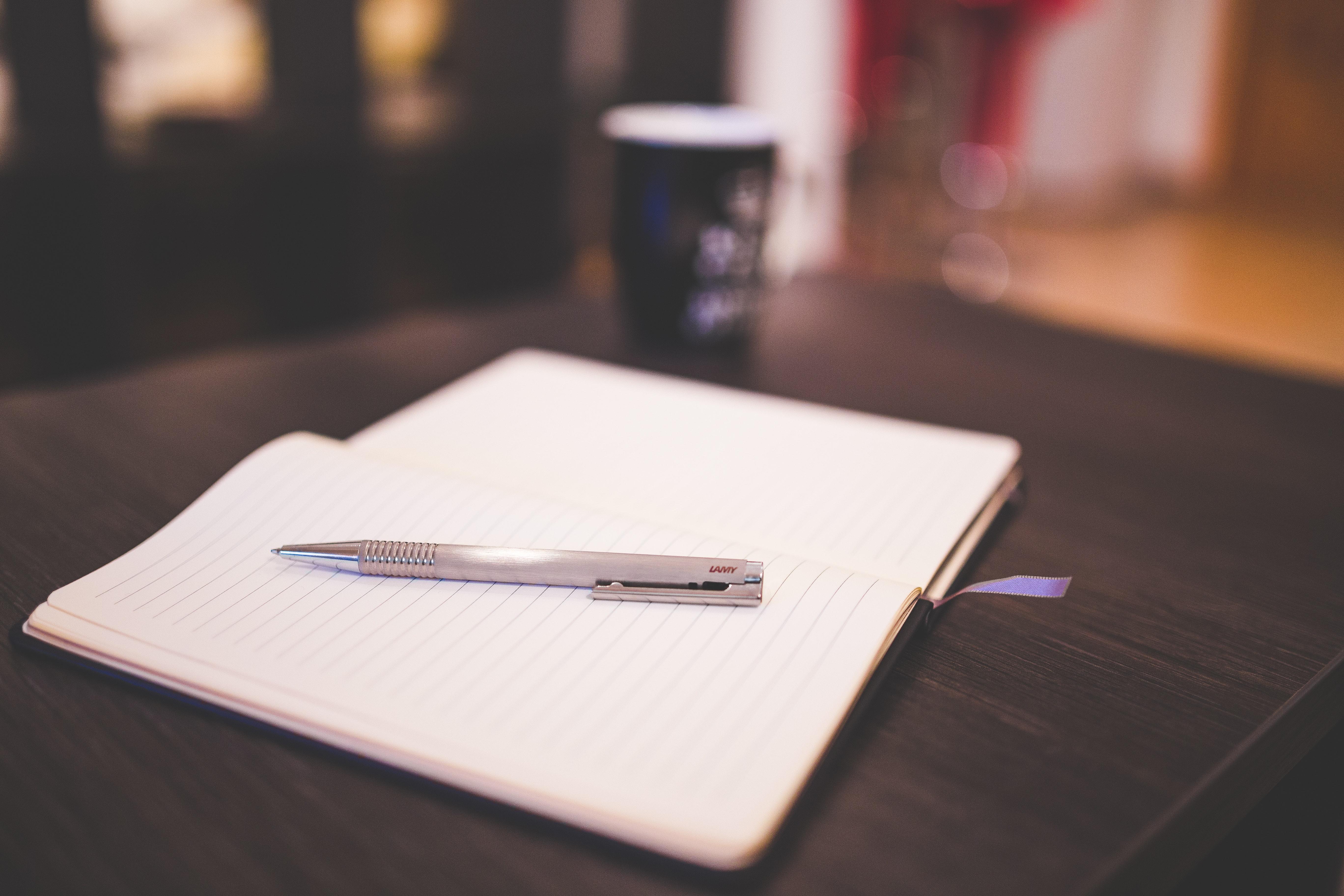 Grey push pen on white notebook photo