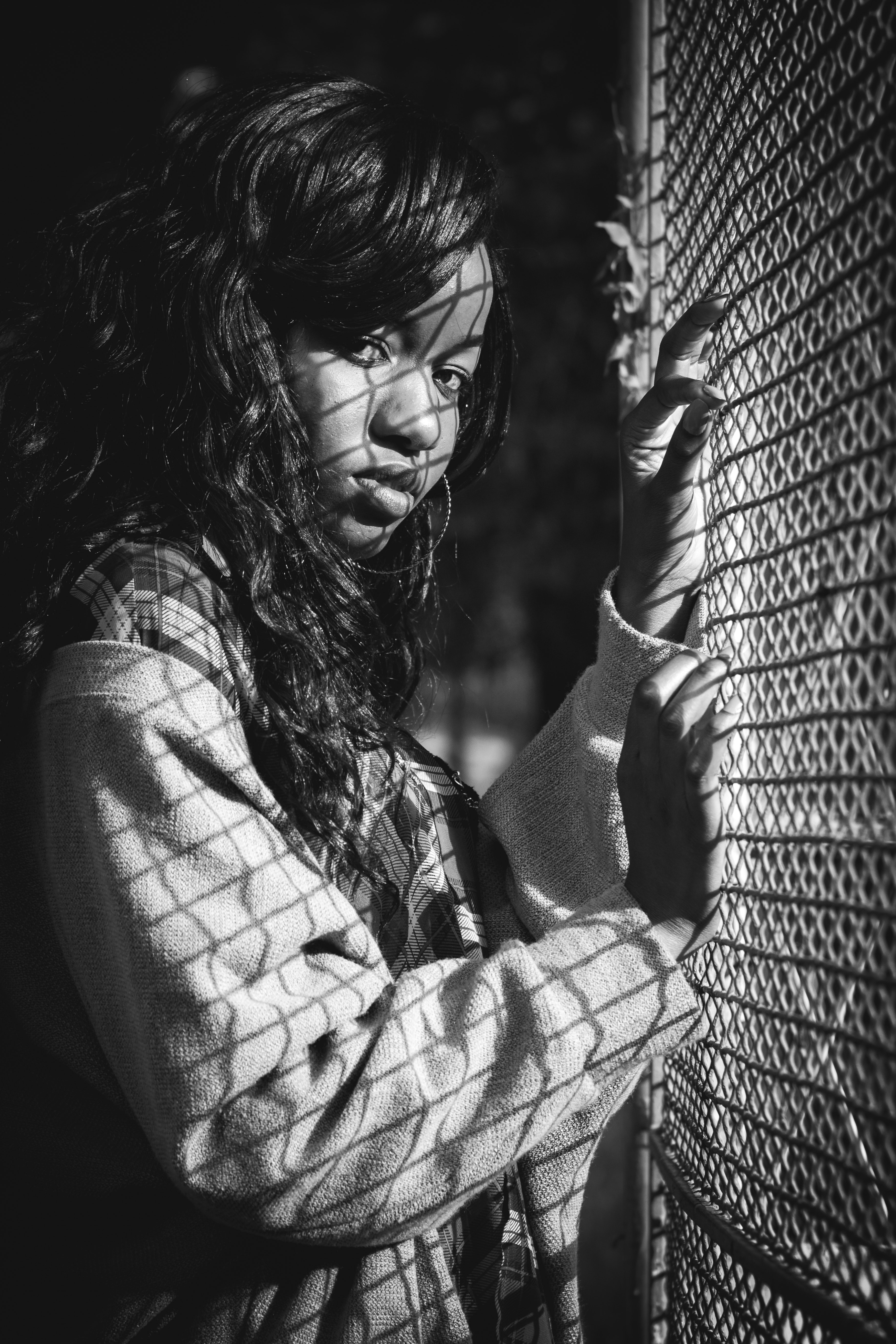 Grey scale photography of woman standing against mesh grill