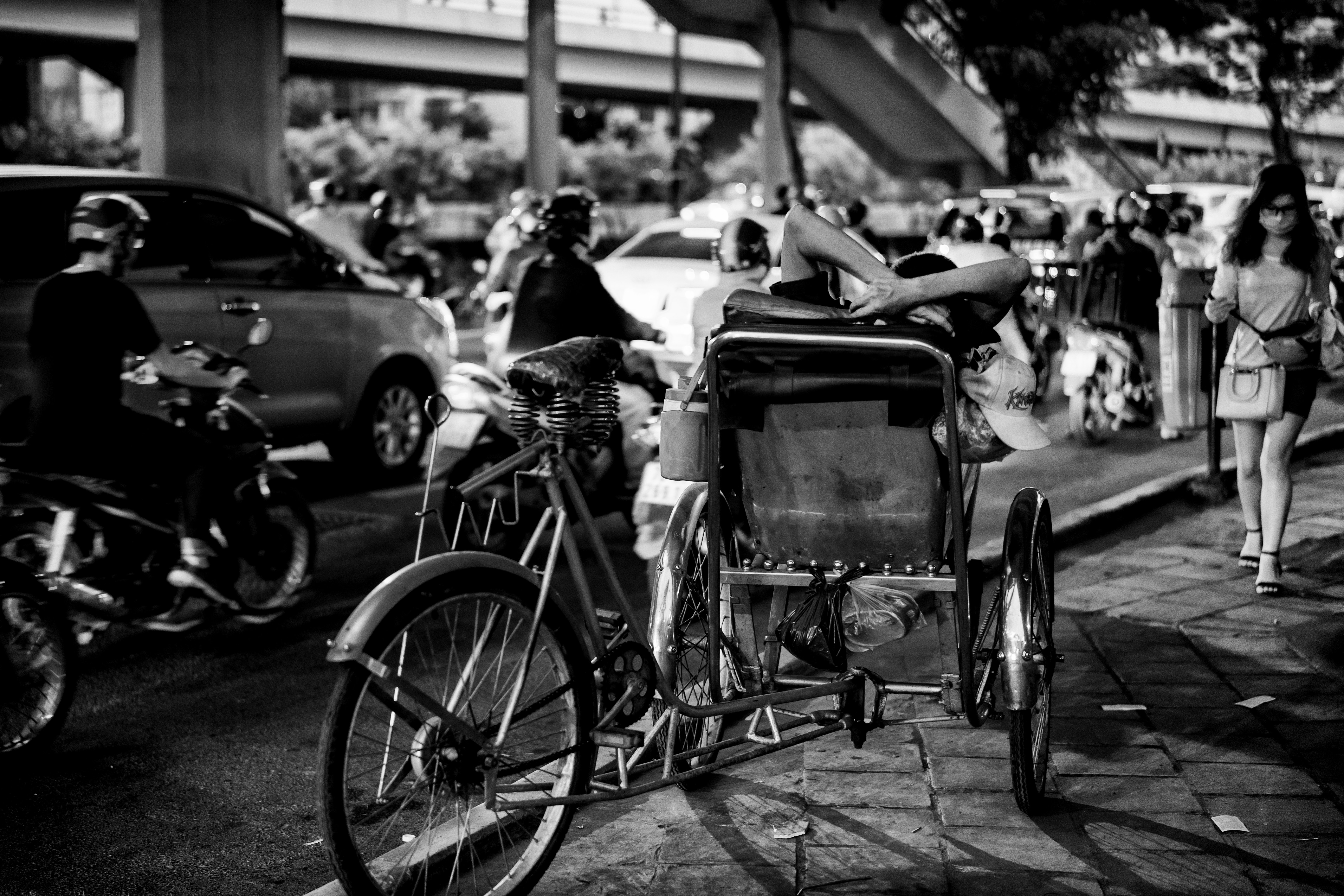 Greyscale photo of man sitting on sidecar of bicycle