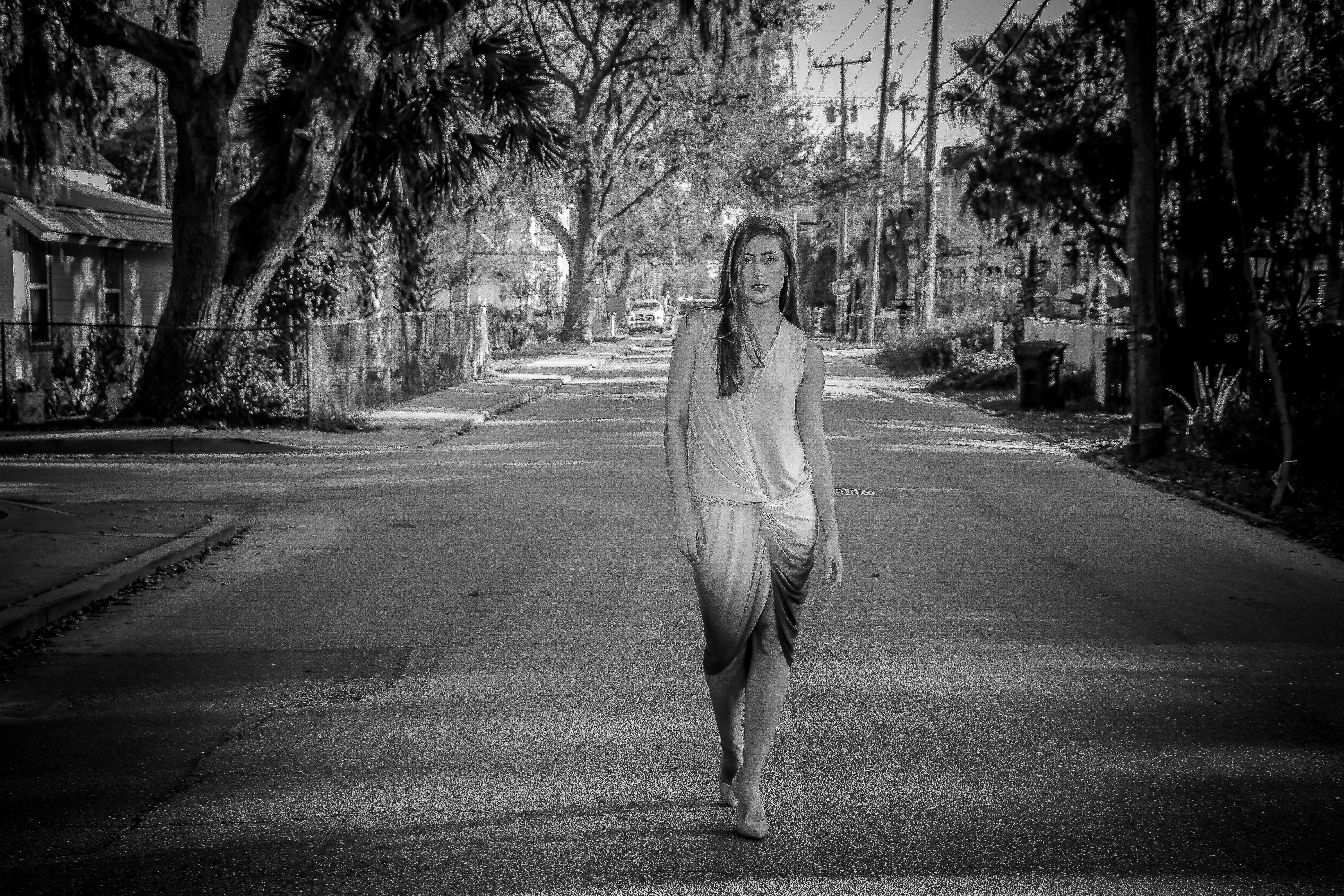 Greyscale photo of woman standing on street