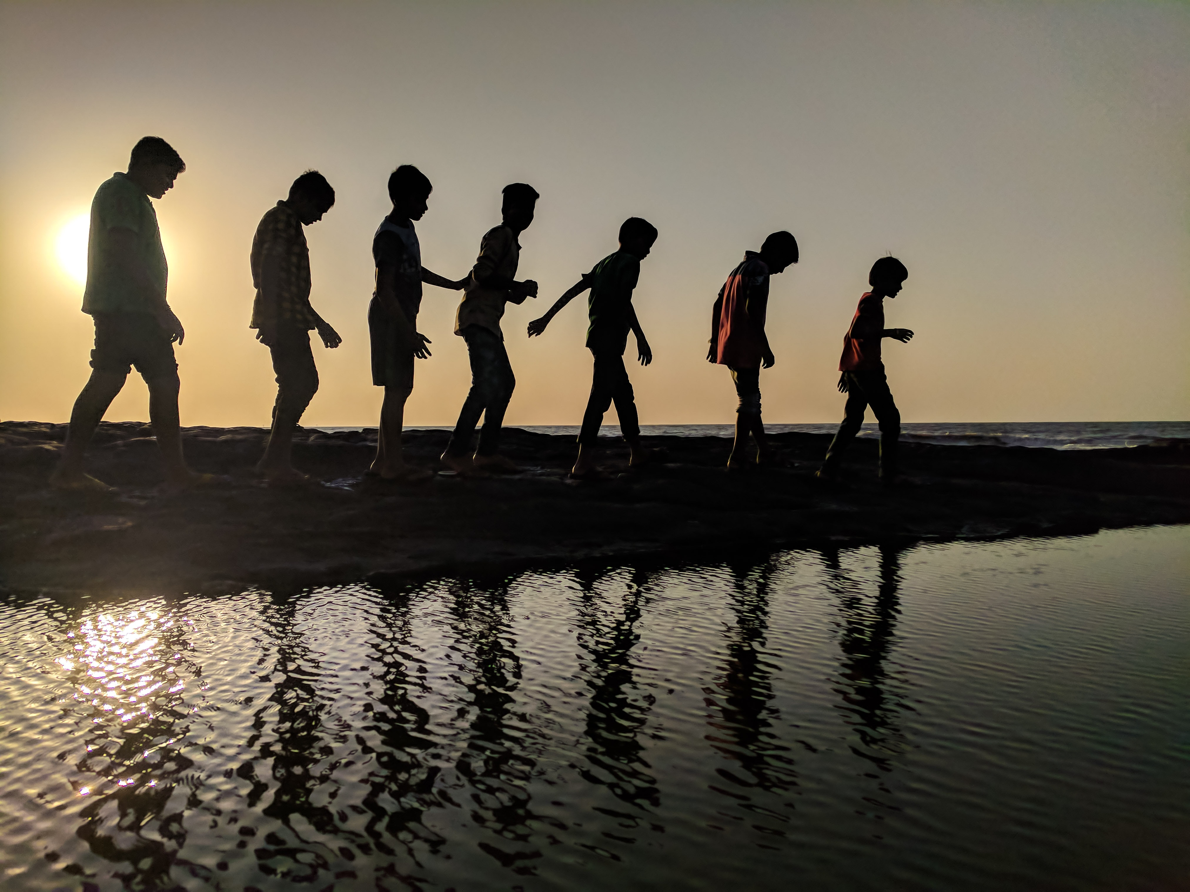 Group of children walking near body of water silhouette photography