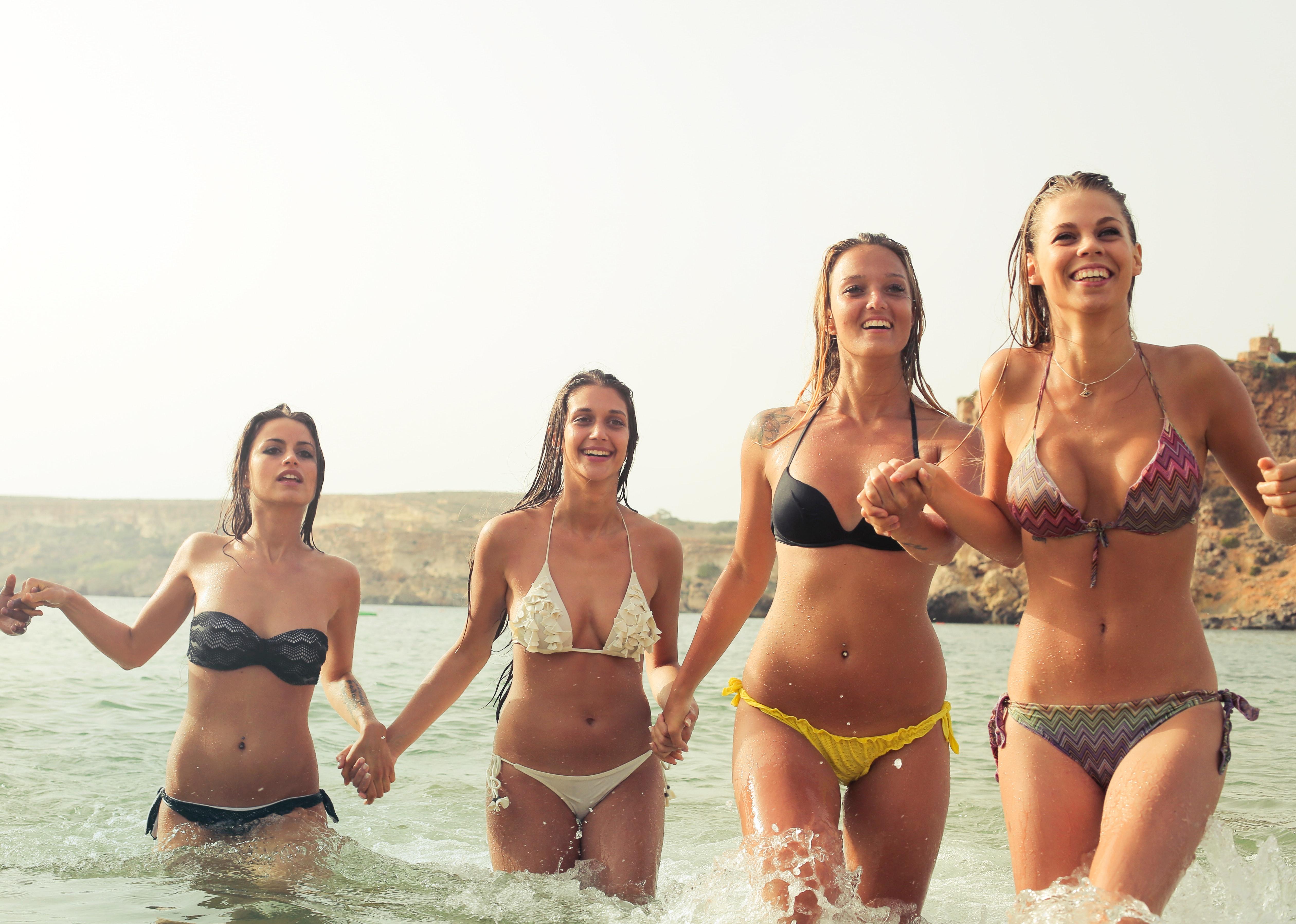 Group of woman wearing bikini on body of water photo