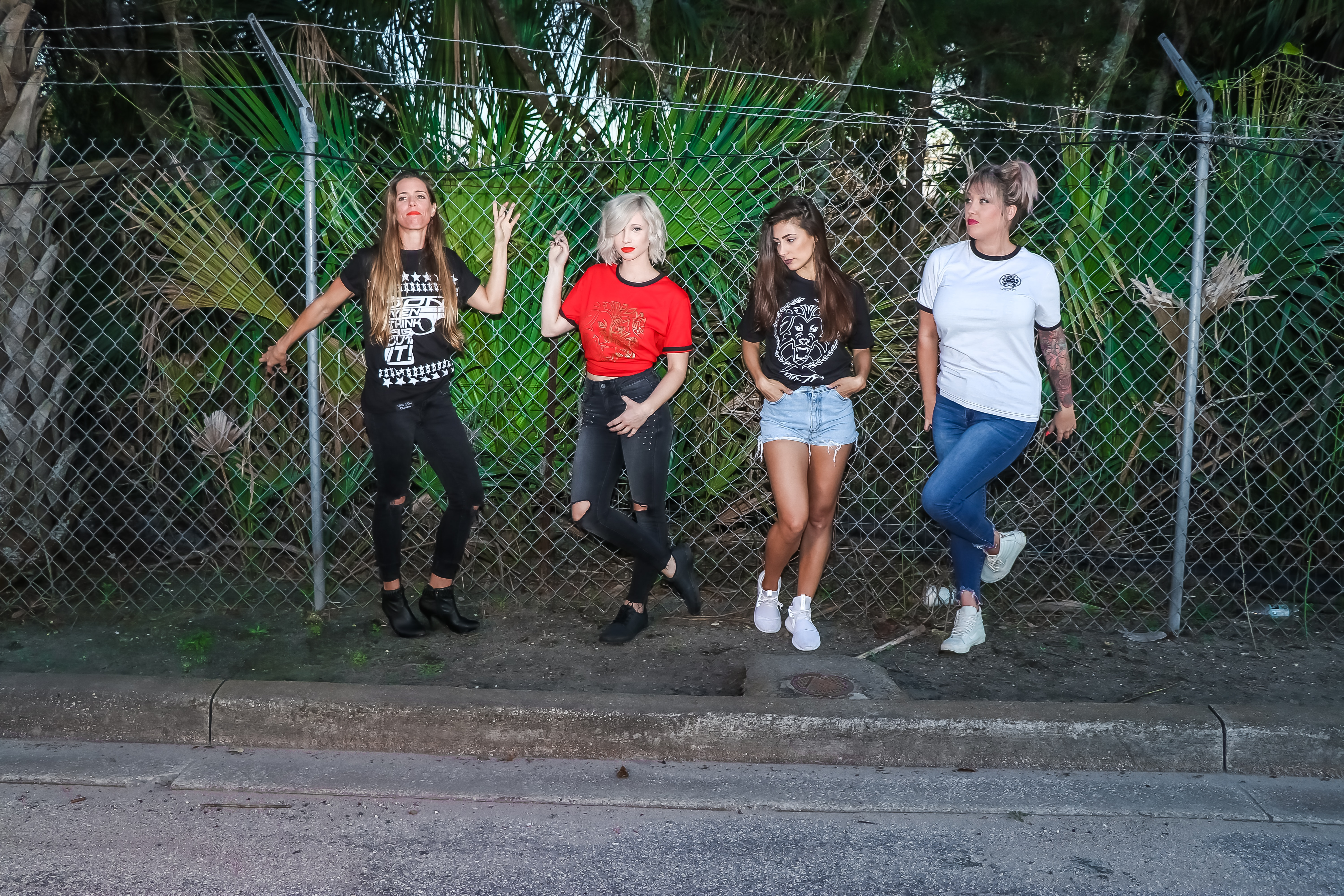 Group of women standing in front metal fence photo