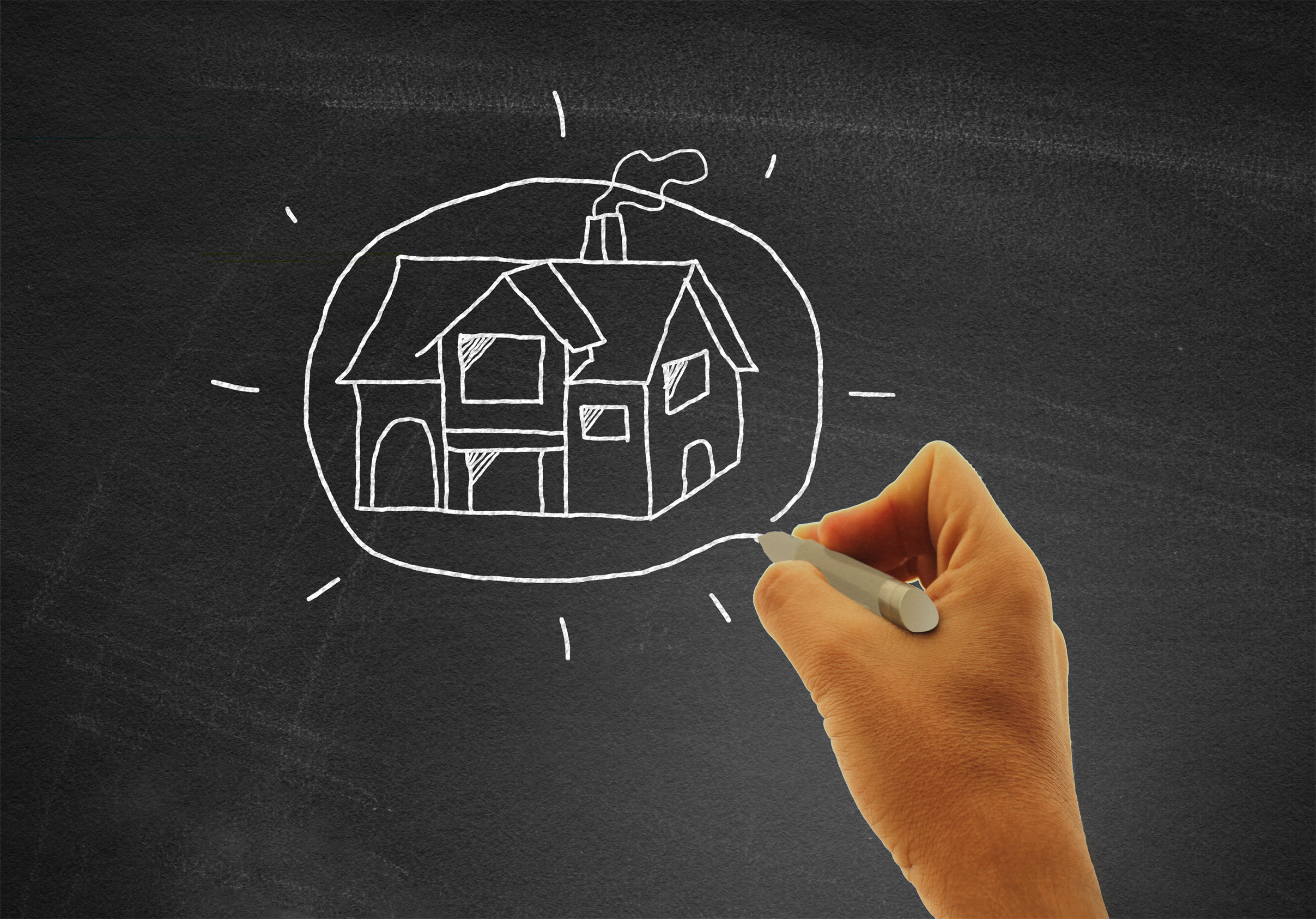 Hand drawing a house on blackboard - real estate and housing concept photo