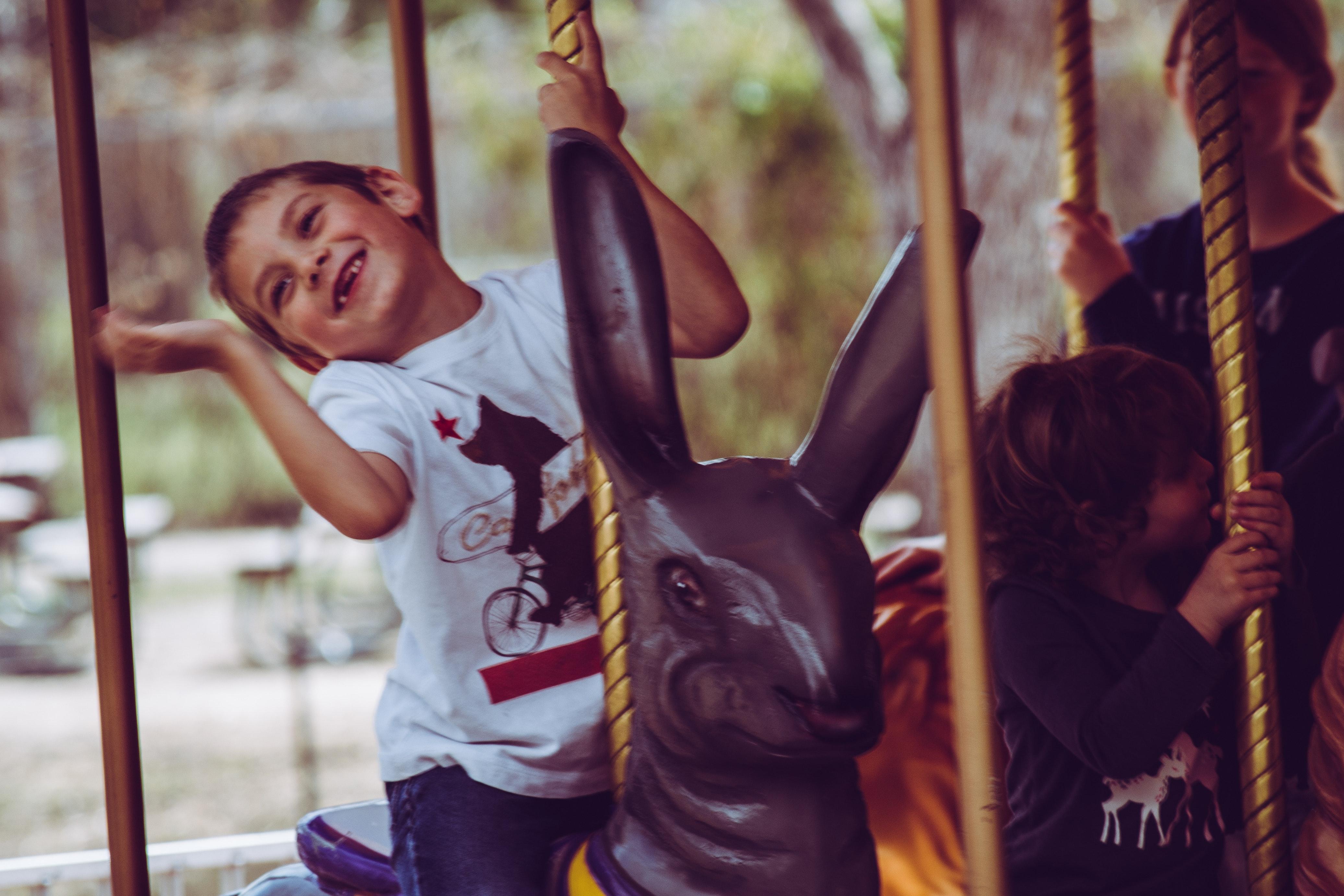 Happy child riding a rabbit carousel photo