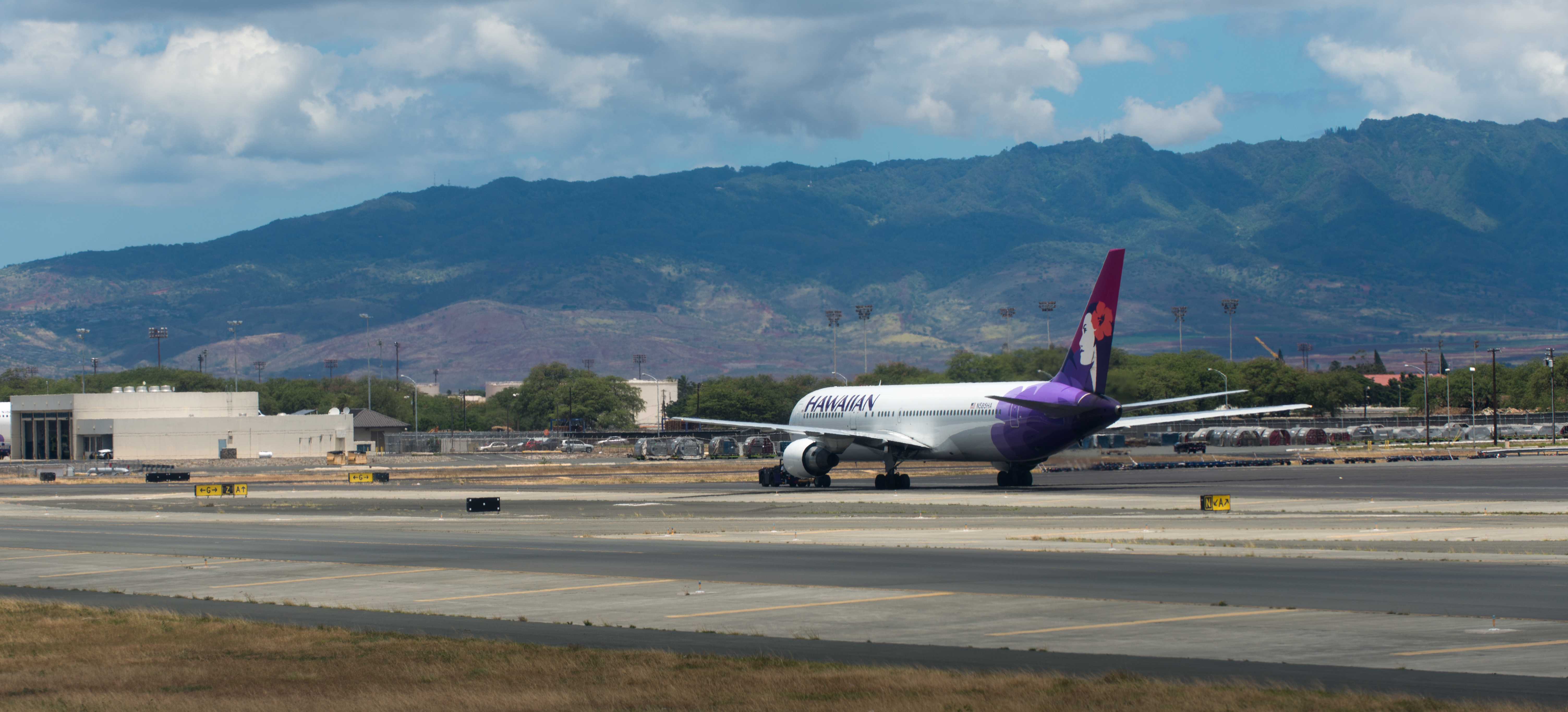 Hawaiian airline plane on tarmac at honolulu international airport in front of hills photo