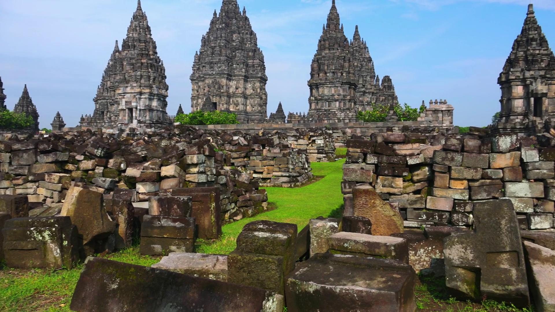 Ancient stone ruins on green field and Candi Prambanan or Rara ...