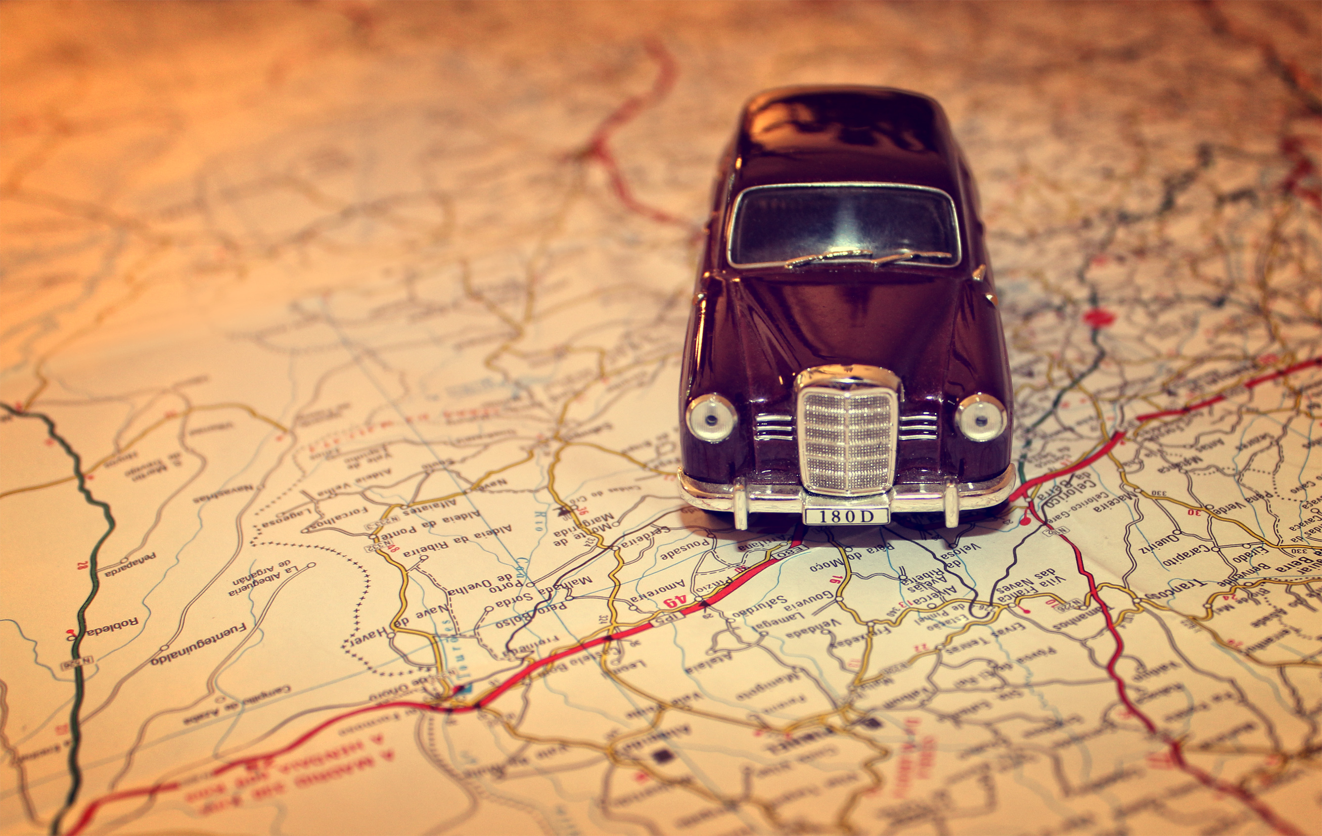 hit the road travel concept with vintage miniature car on road map