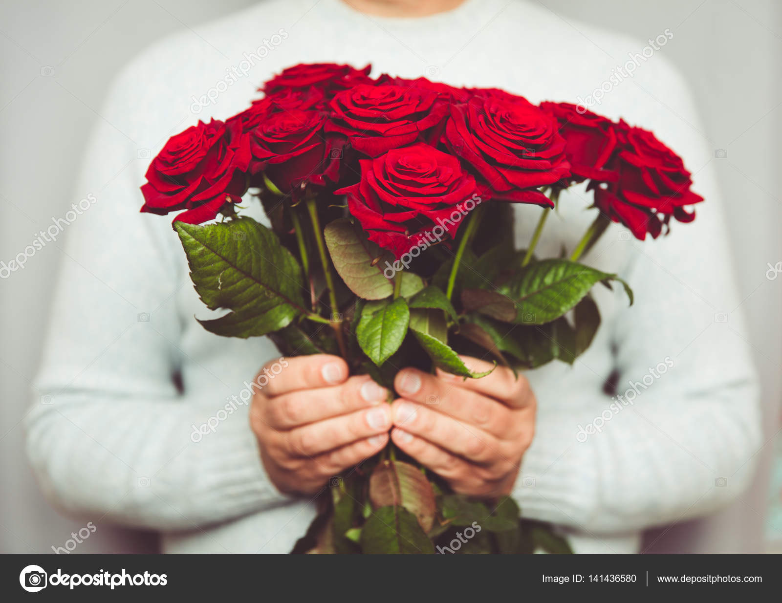 Handsome man holding Bouquet of beautiful red roses in hand — Stock ...