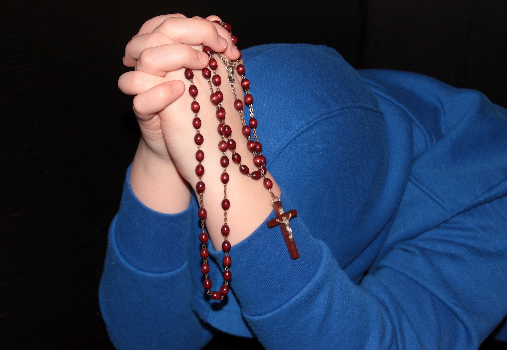 Holding string of beads - praying photo