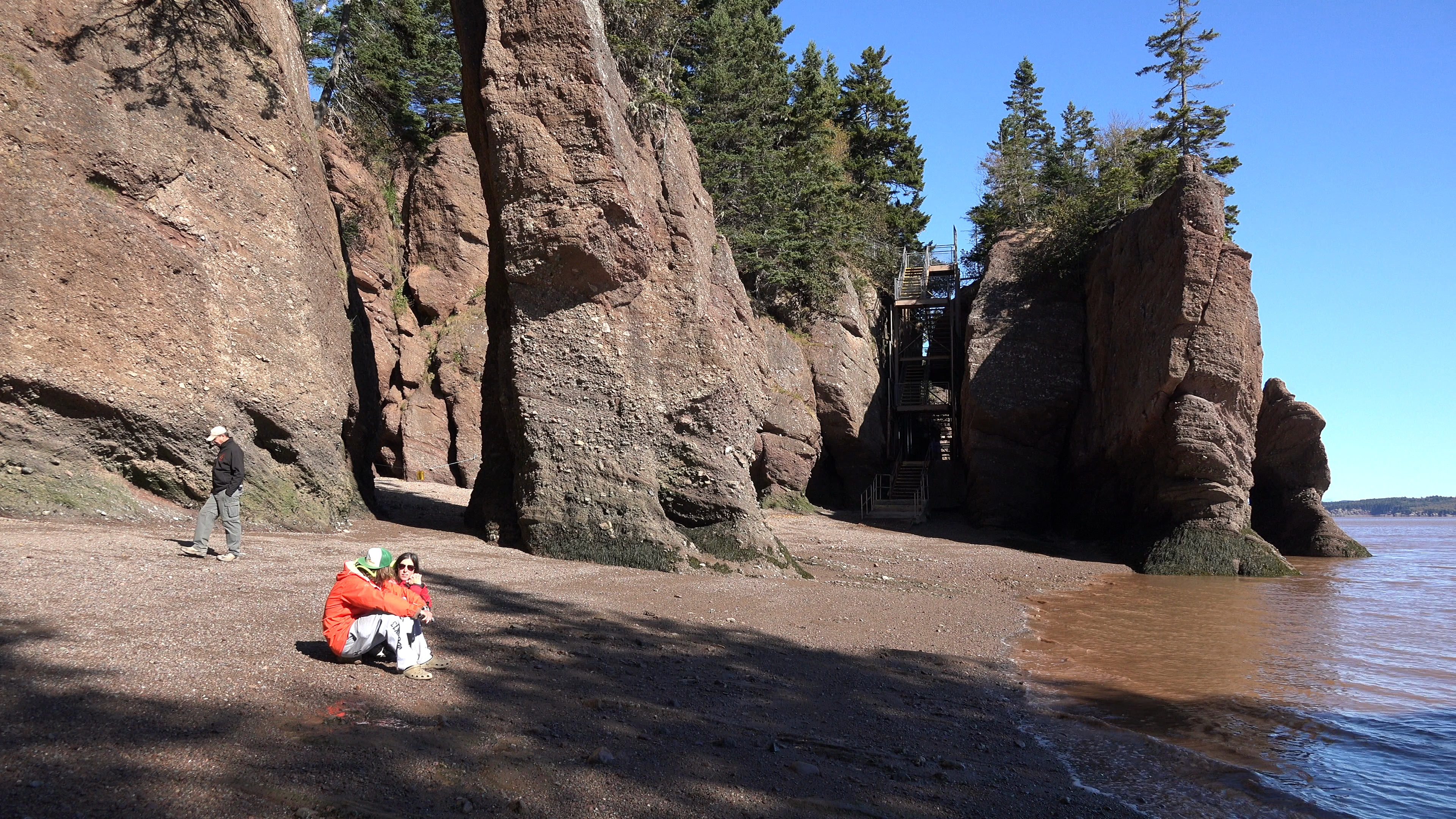 Canada women sitting on beach at Hopewell Rocks ~ Video #86493915