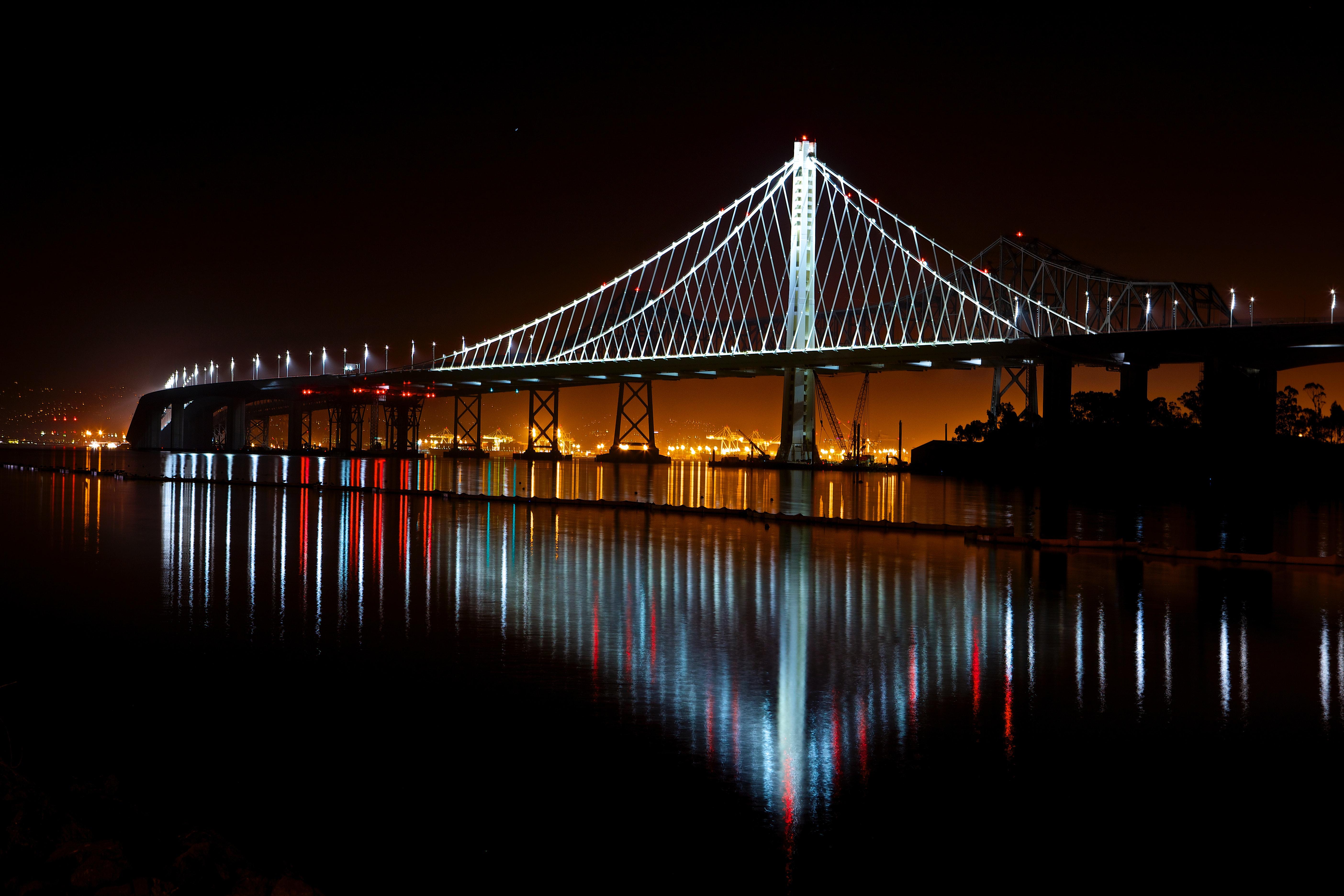 Illuminated suspension bridge against sky at night photo