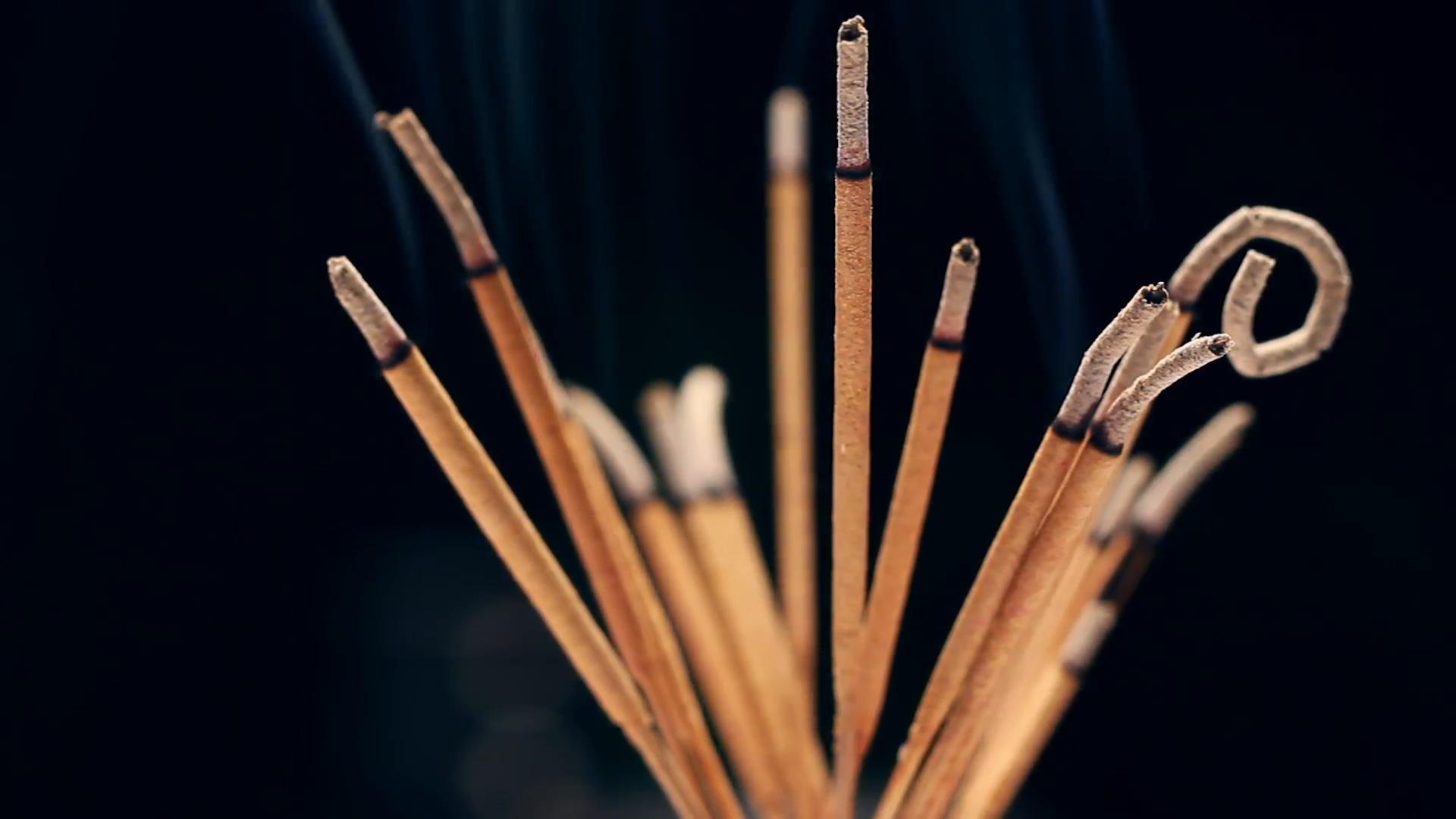 Close up of burning incense sticks with smoke over black background ...