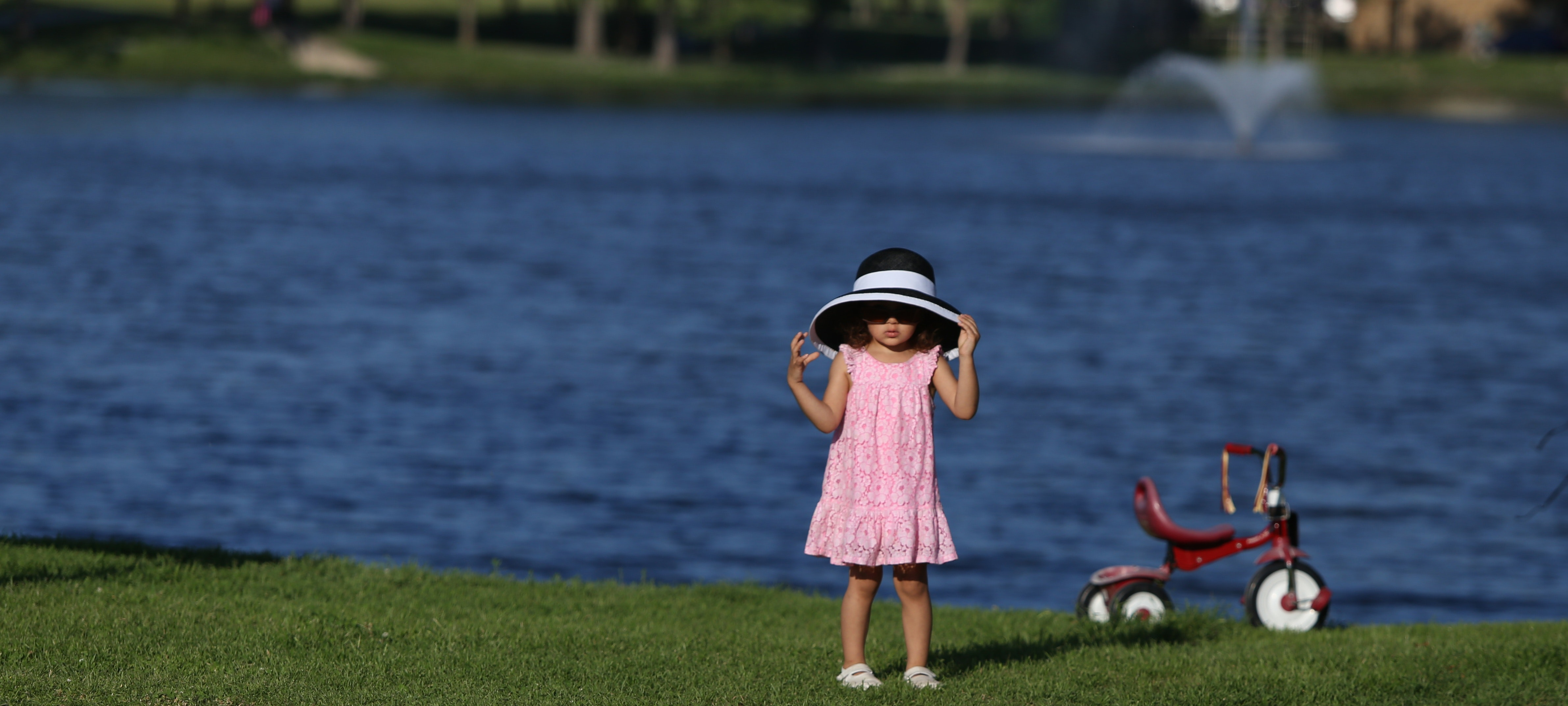 Kid in pink dress with white and black sun bucket hat beside the red pedal trike in front of body of water photo