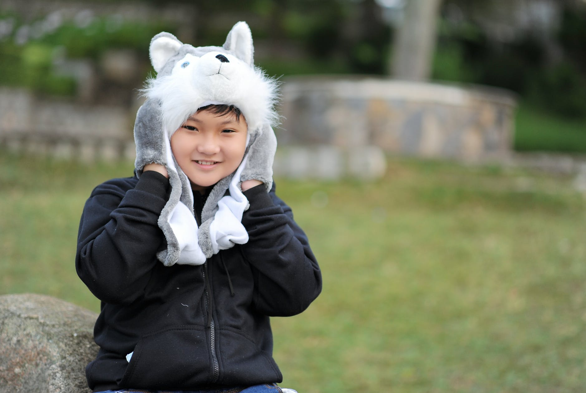 Kid wearing gray wolf critter hat and black jacket photo