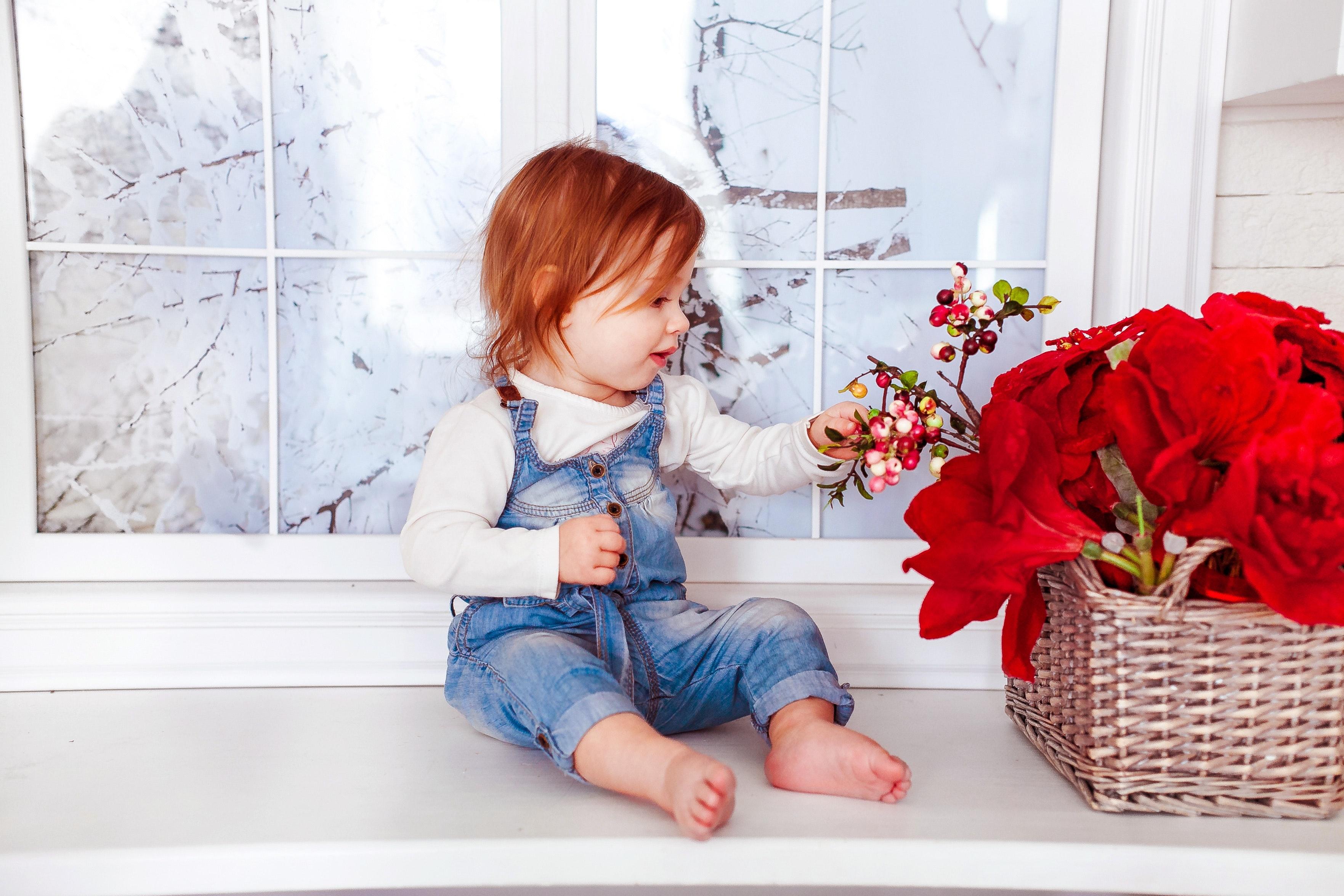 Kid's blue denim jumper sitting on white wooden side table photo