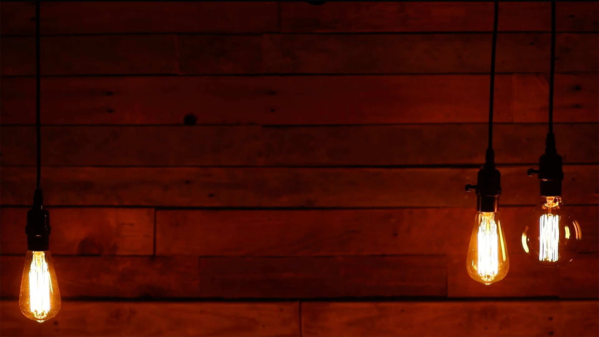 Three Urban Retro Low Hanging Light Bulbs on Wood Background Loop ...