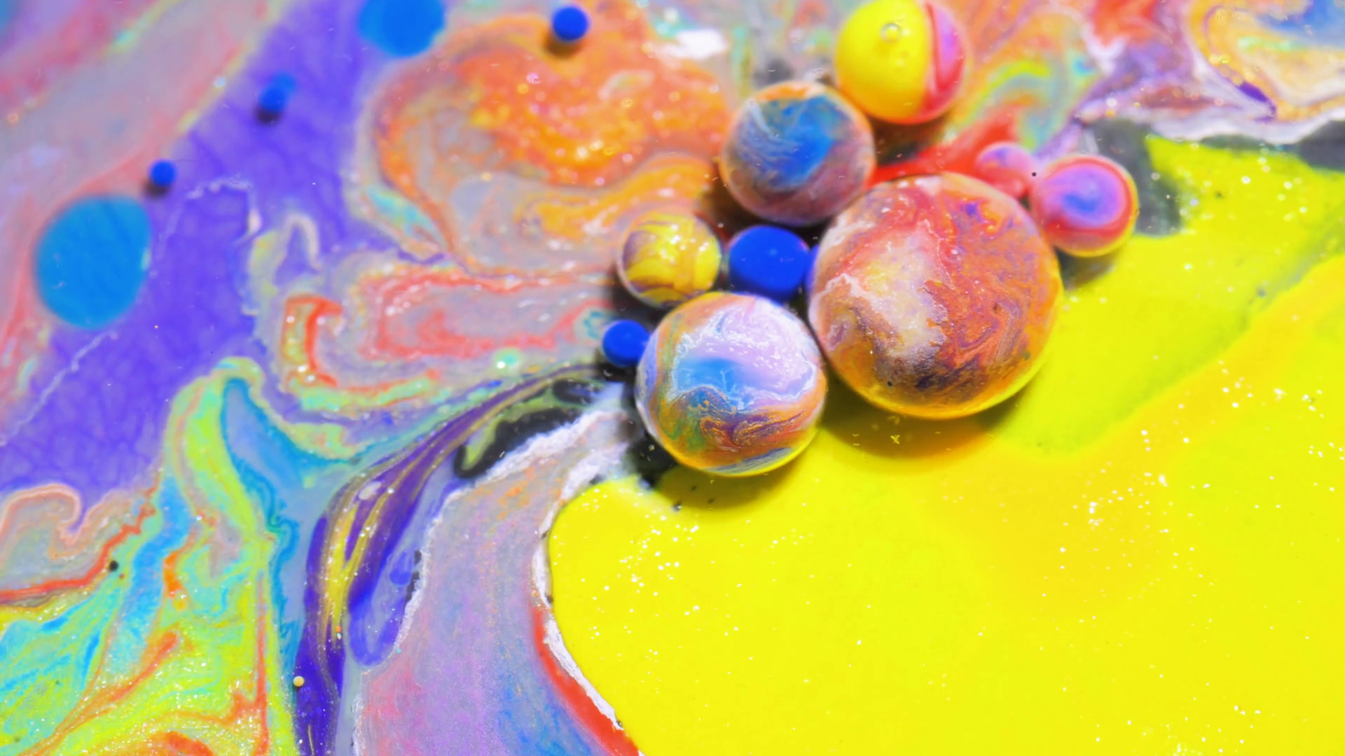 Liquid colors,yellow and red, mix underwater into orange. Bubbles ...