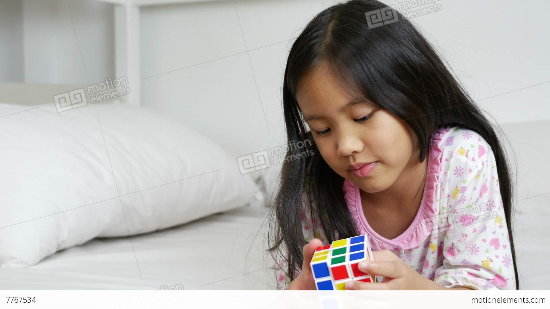 4K Video : Little Asian Girls Playing Rubik Cube On The Bed Stock ...