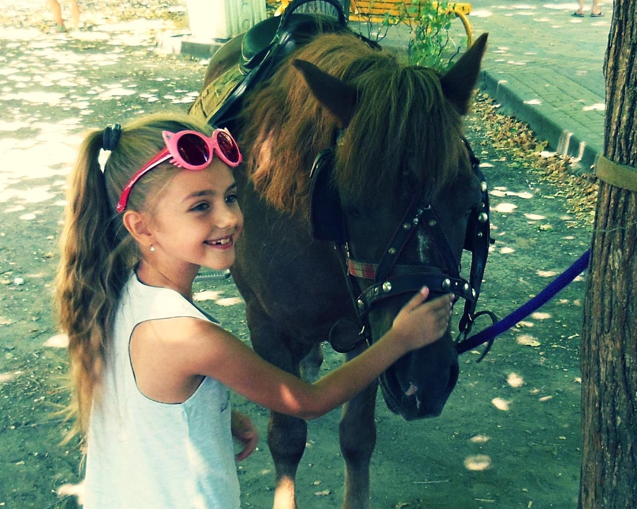 Little girl petting horse photo