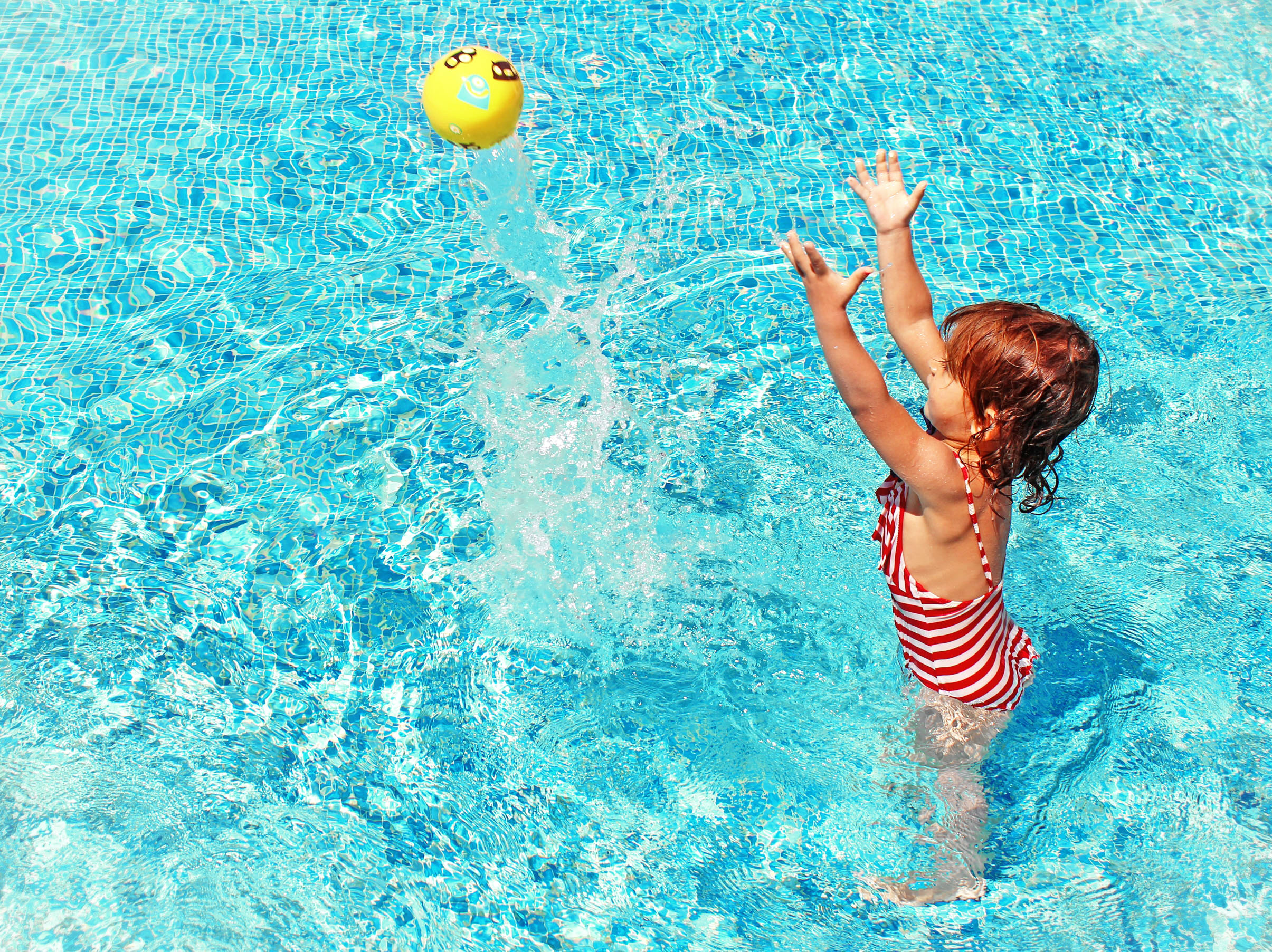 Little girl playing with a ball in the swimming pool photo