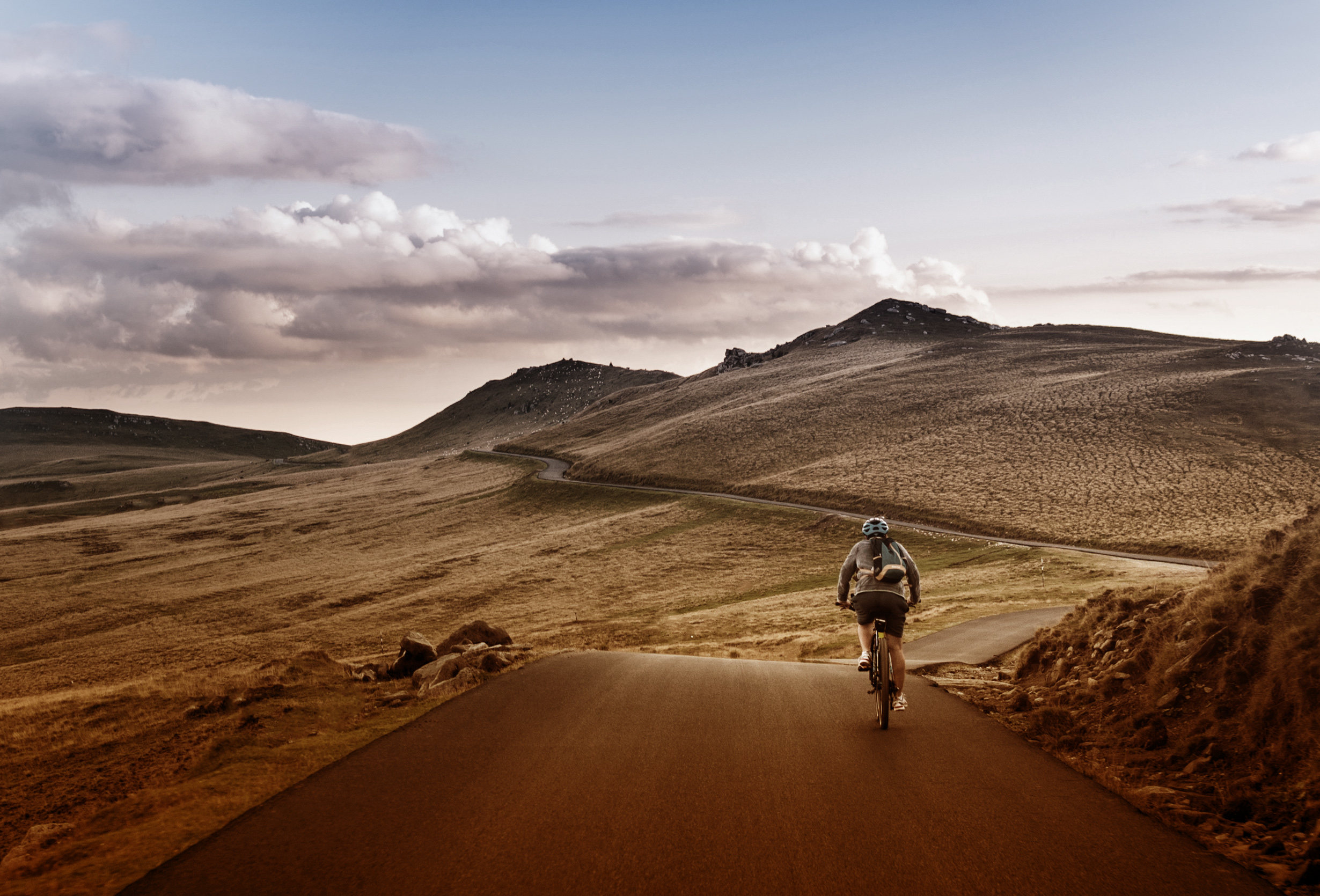 Lone biker on the road through mountains photo
