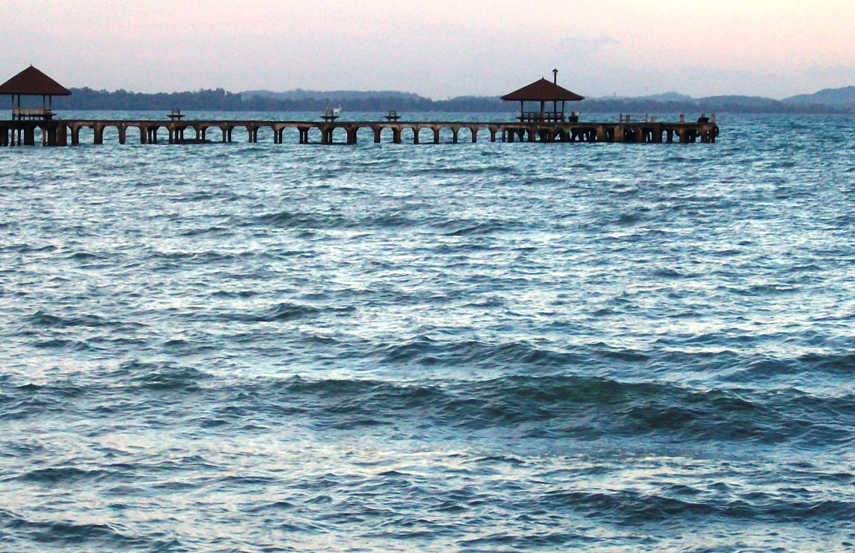 Long wooden tropical pier at sunset photo