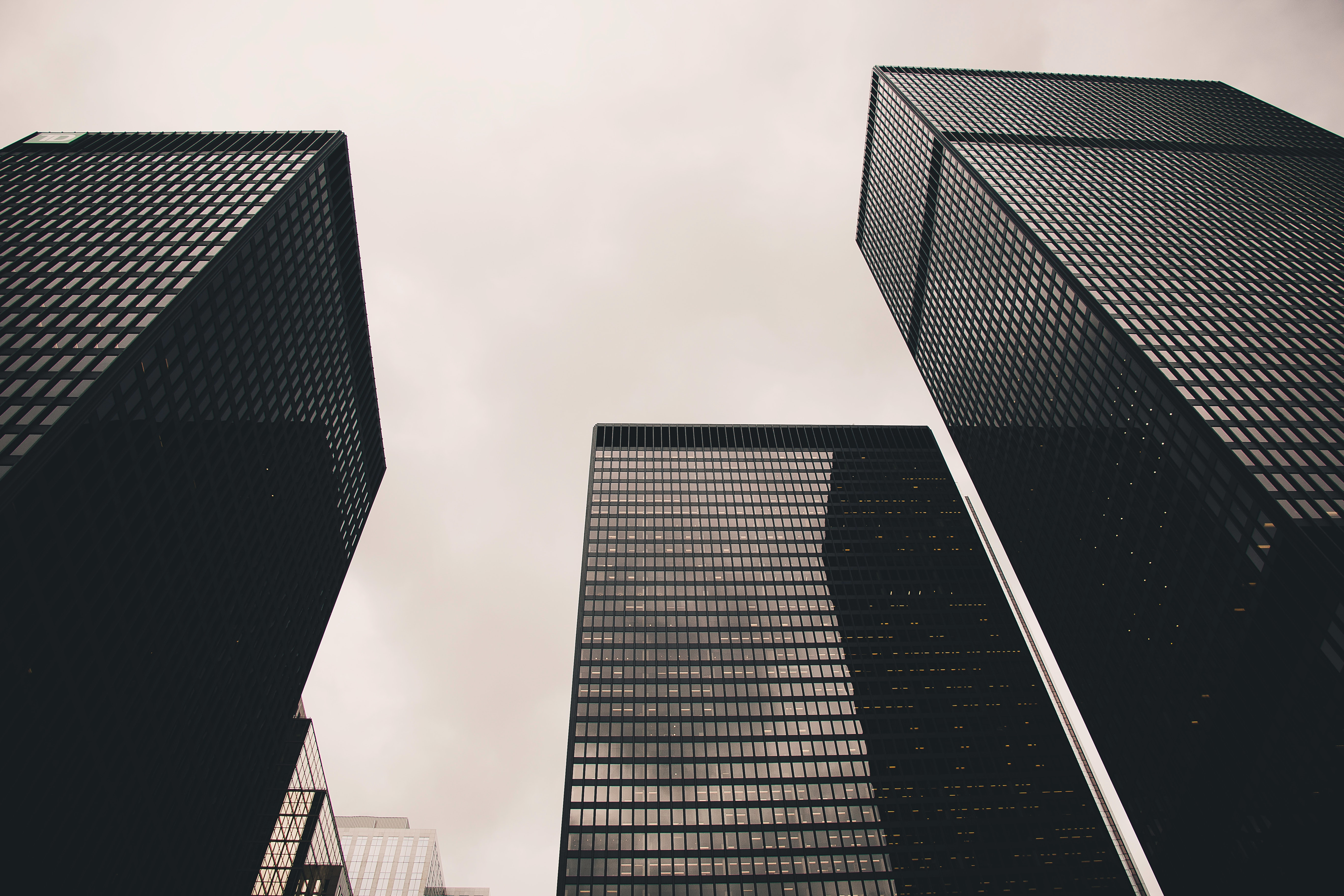 Low angle photography of black high rise building under nimbus clouds background