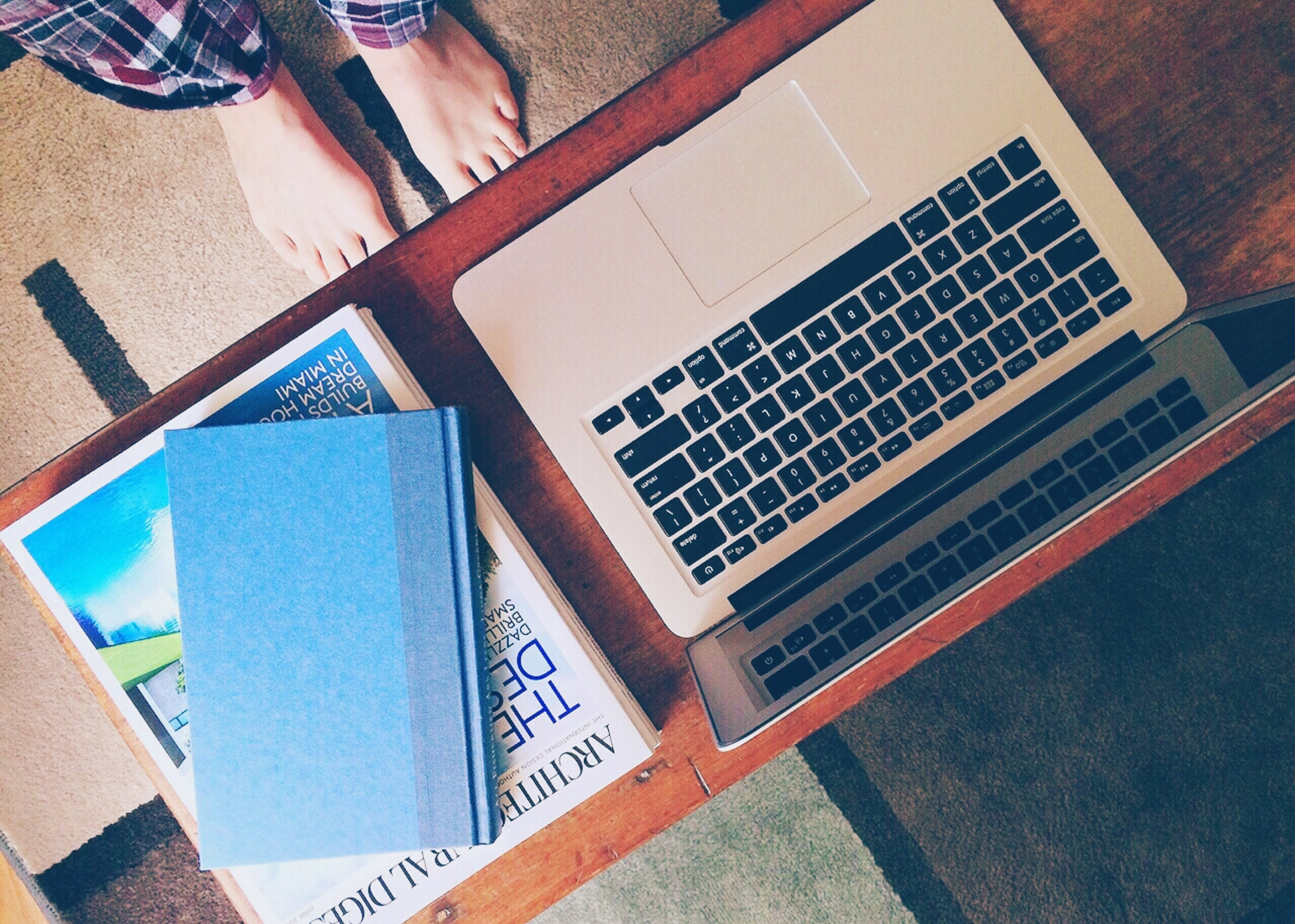 Macbook air beside 2 books on table photo