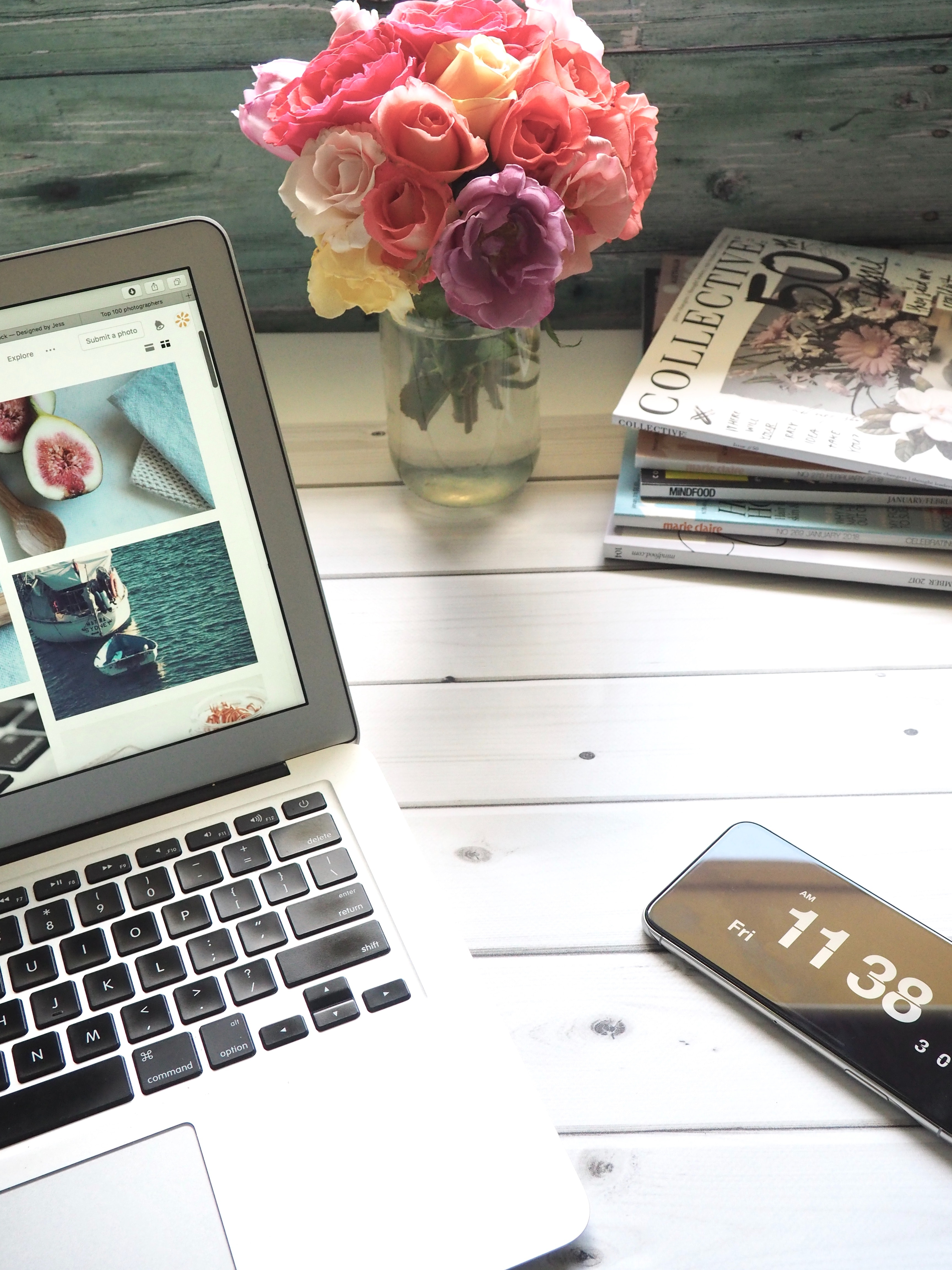 Macbook air, flower bouquet and magazines on white table photo
