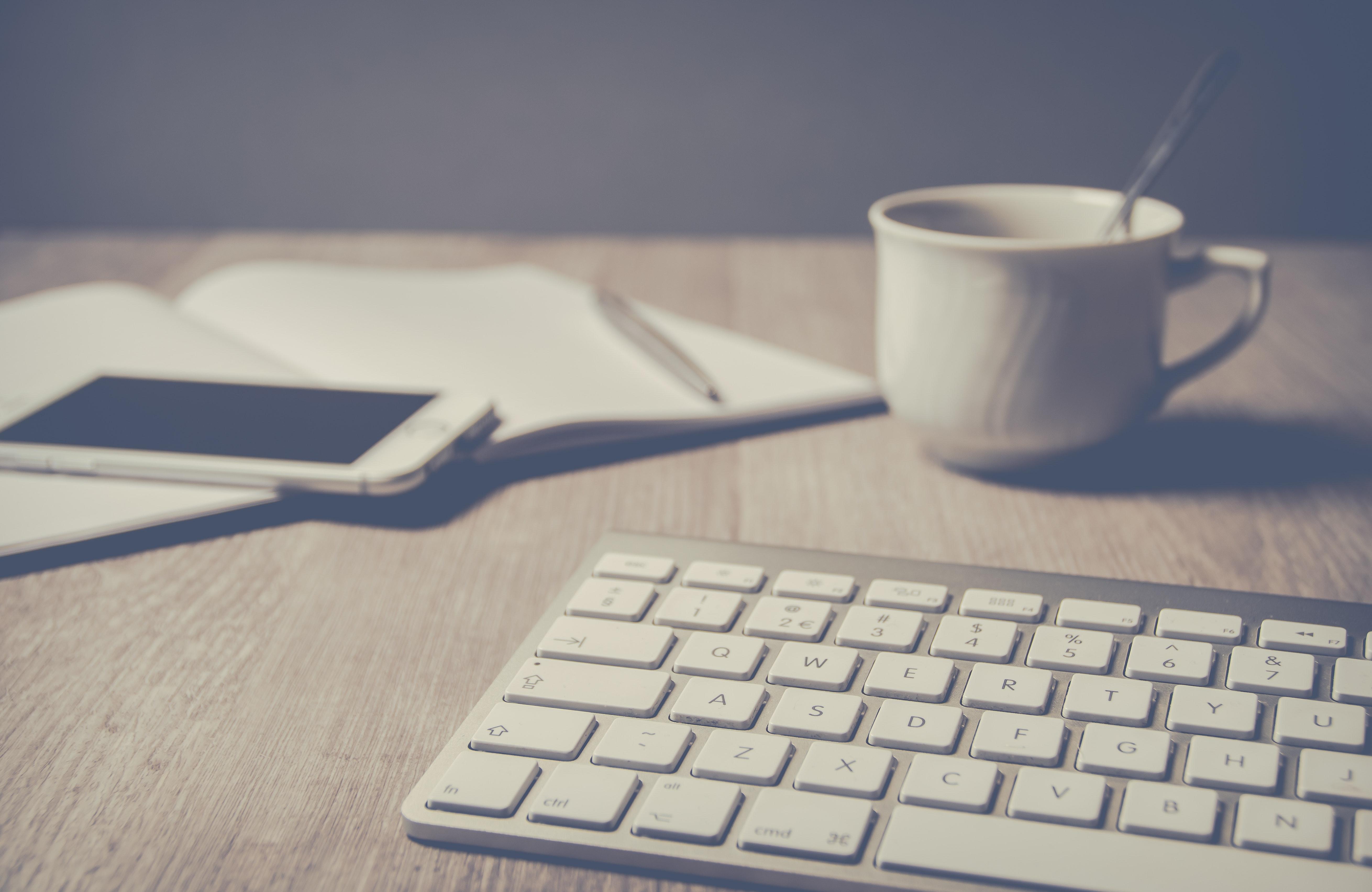 Magic keyboard beside coffee mug on desk photo