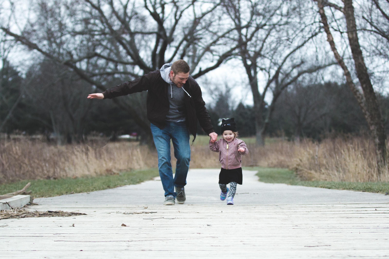 Man and girl running on asphalt road photo