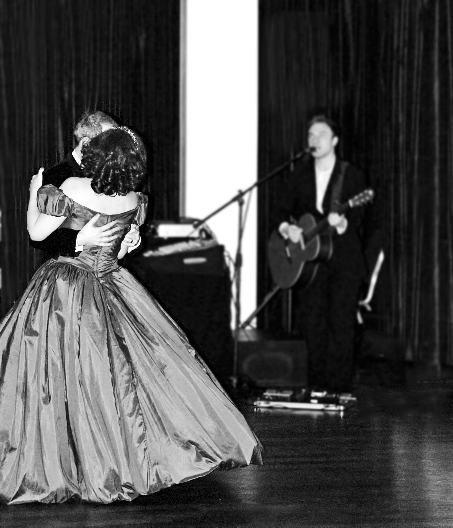 Man and woman dancing in prom apparel near man singing photo