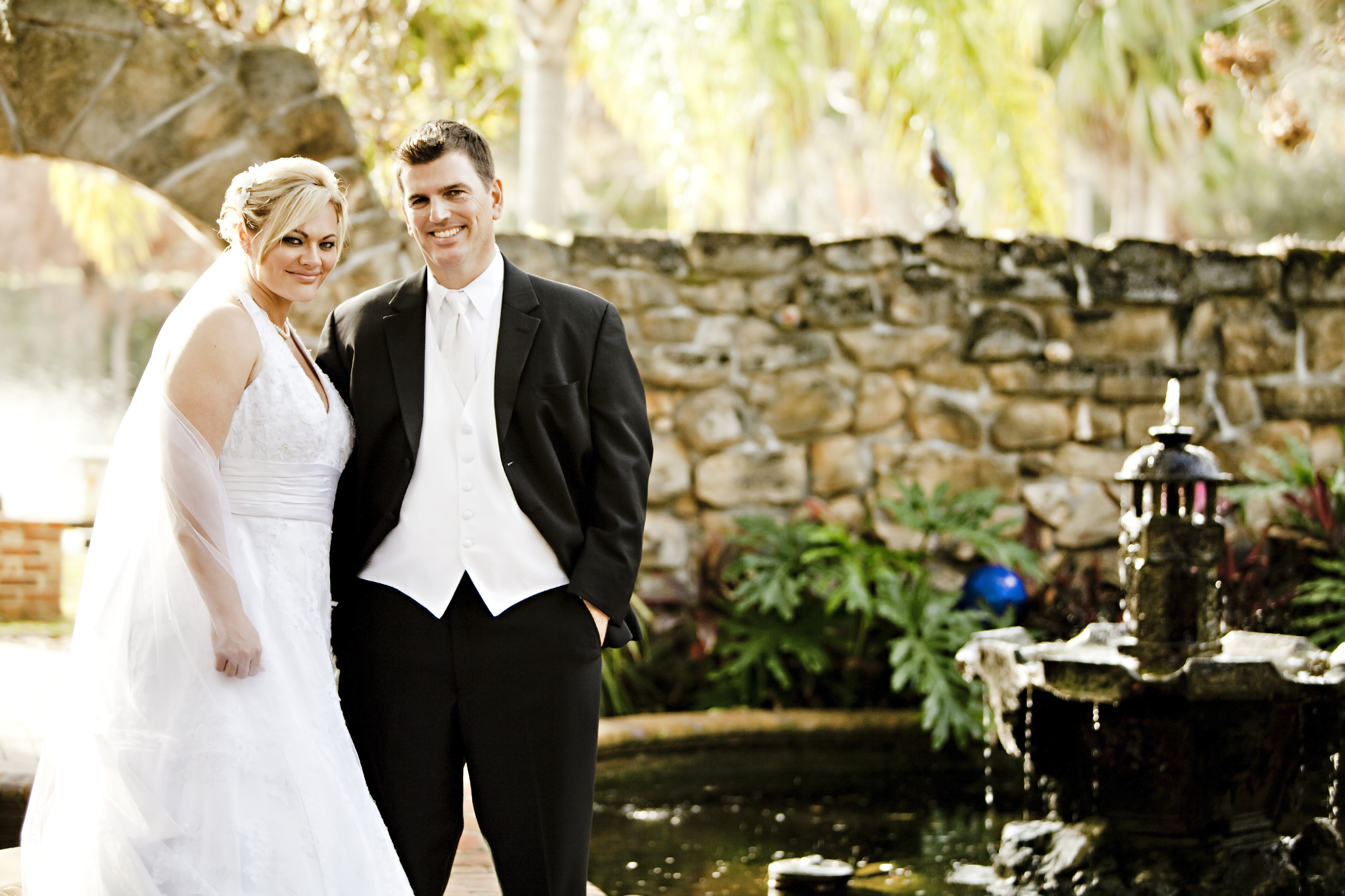 Man and woman in their wedding outfit with brown wall in the background near fountain and pond during daytime photo