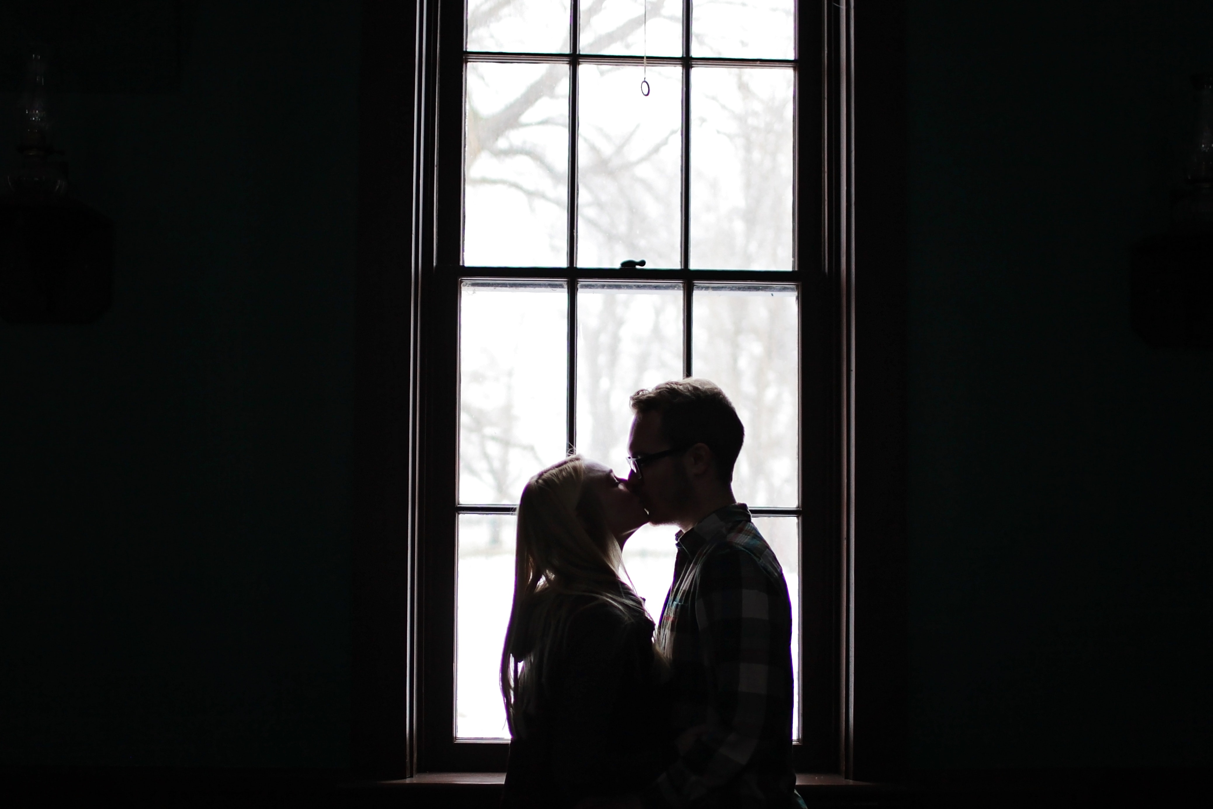 Man and woman kissing beside window photo