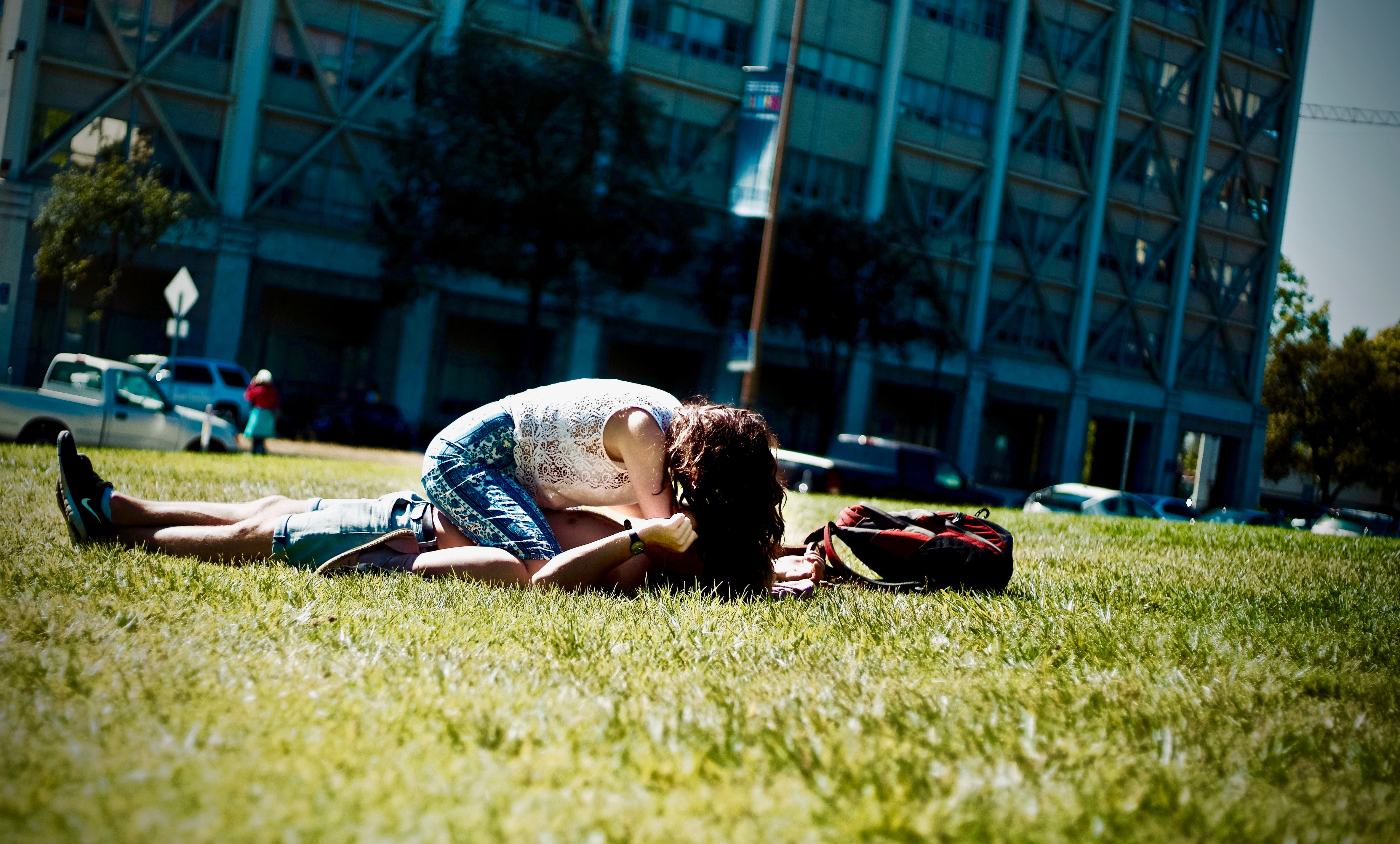 Man and woman lying on green field photo