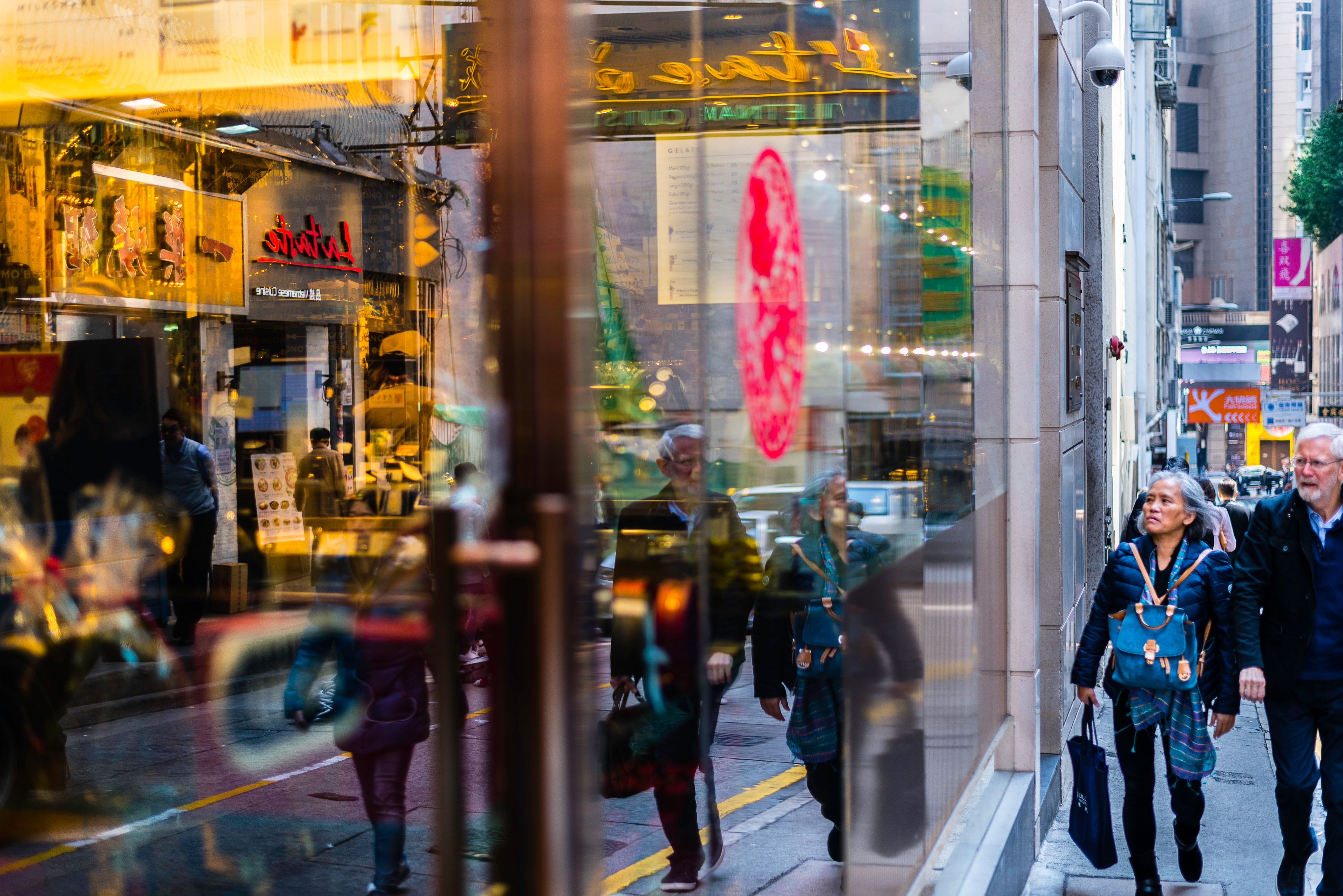 Man and woman passing through building with glass facade photo