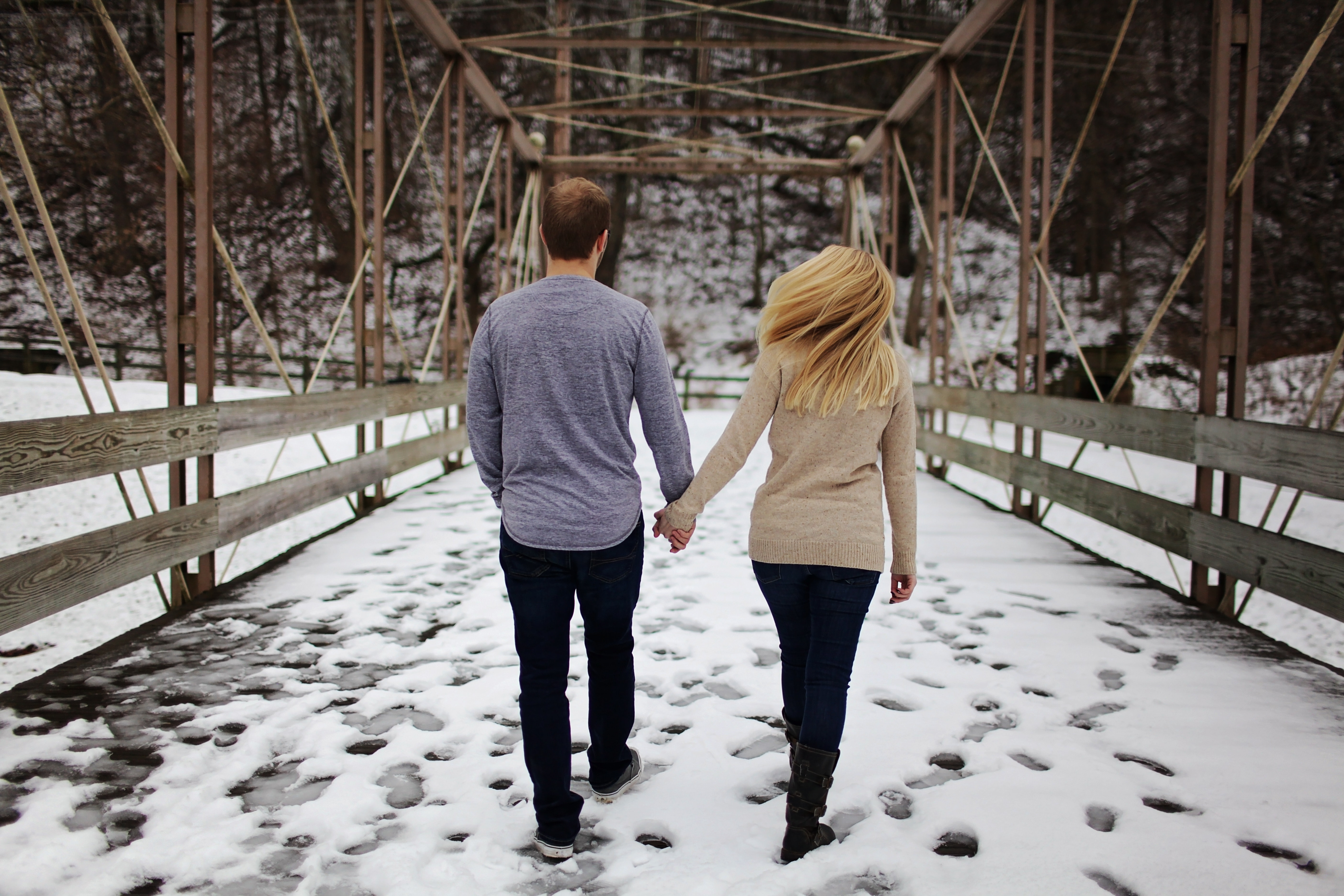 Man and woman walking on snow covered road photo