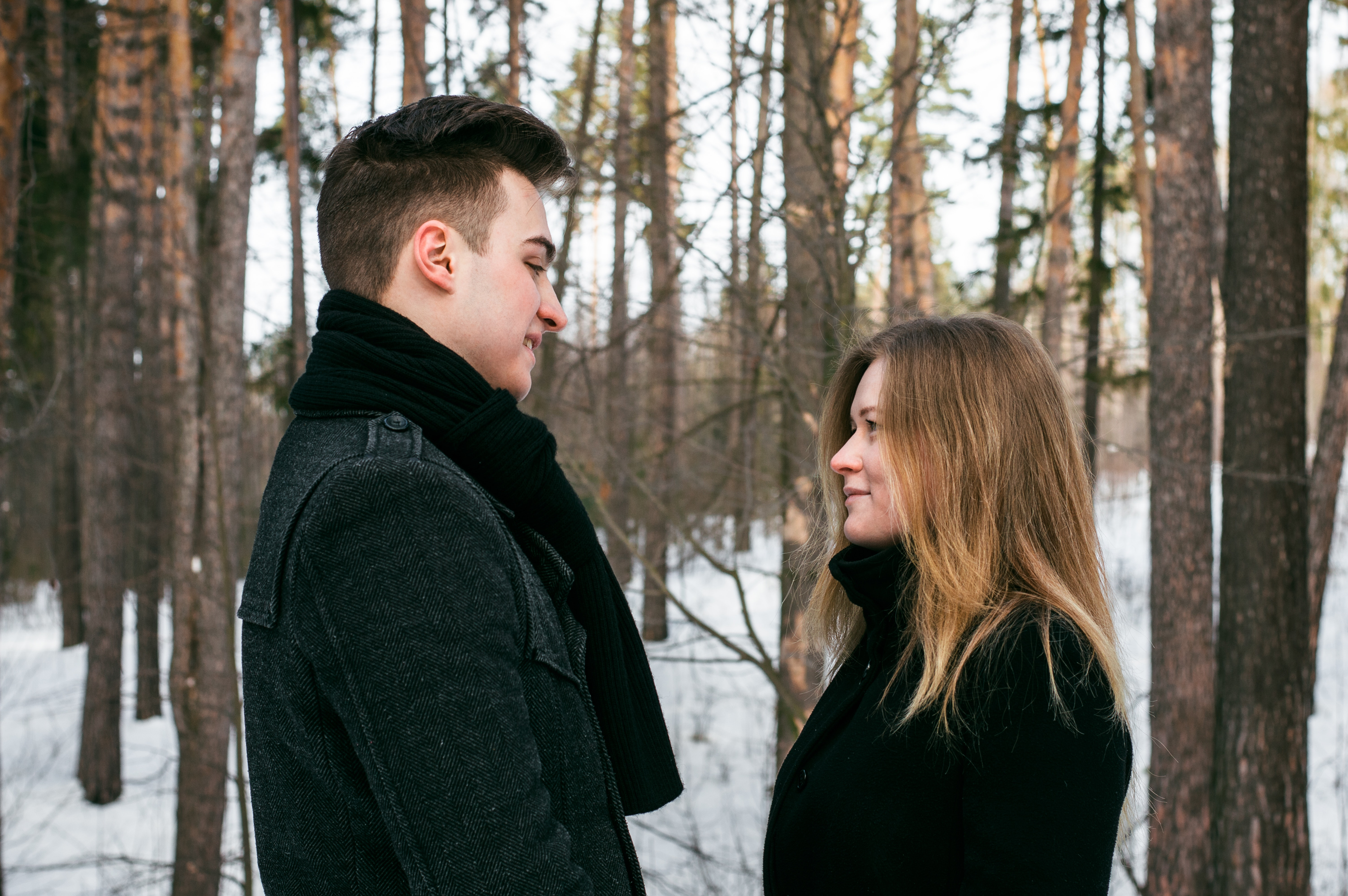 Man and woman wearing black coats standing near snow-covered trees photo