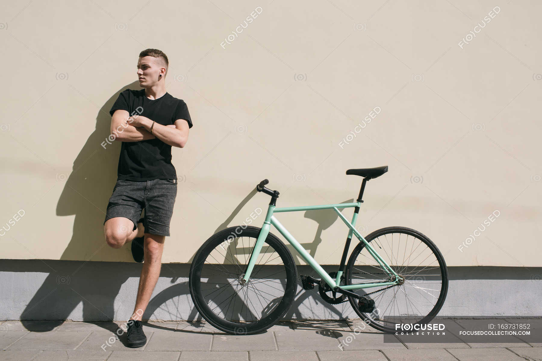 Boy leaning on wal beside bike — Stock Photo | #163731852