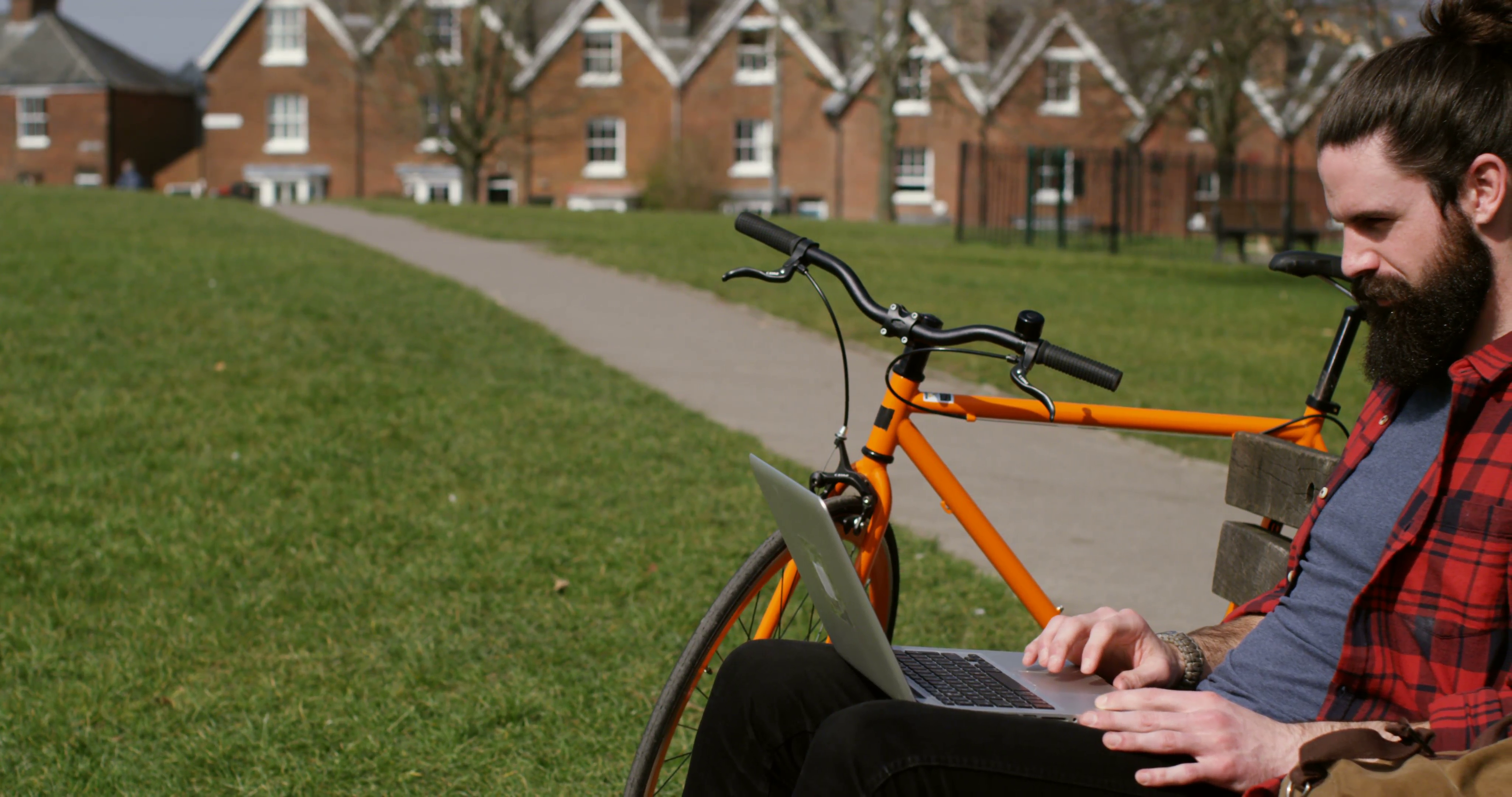 4k, A young man using a laptop in a park with his bicycle beside him ...