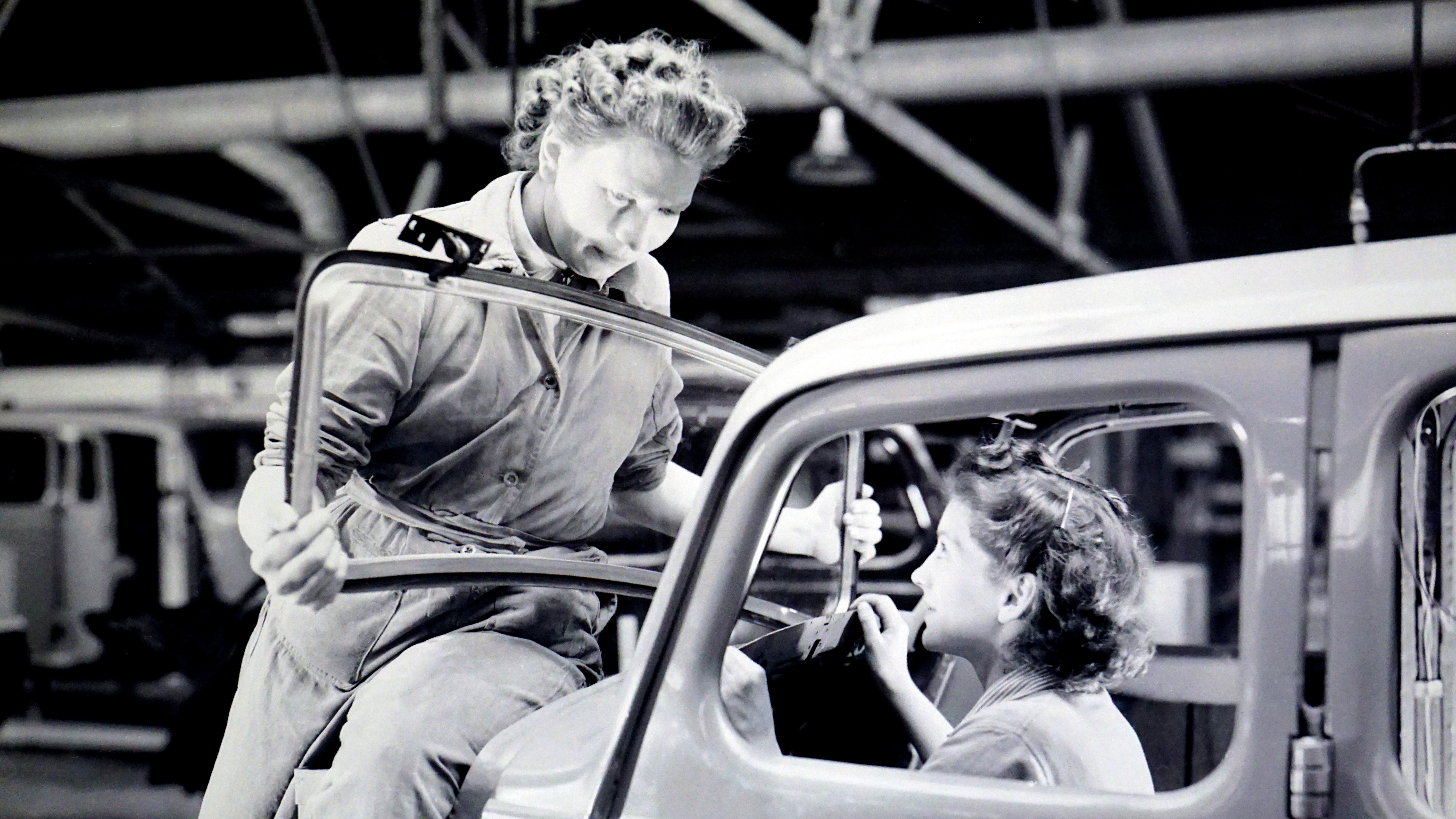 Man carrying car windshield with woman inside a car photo