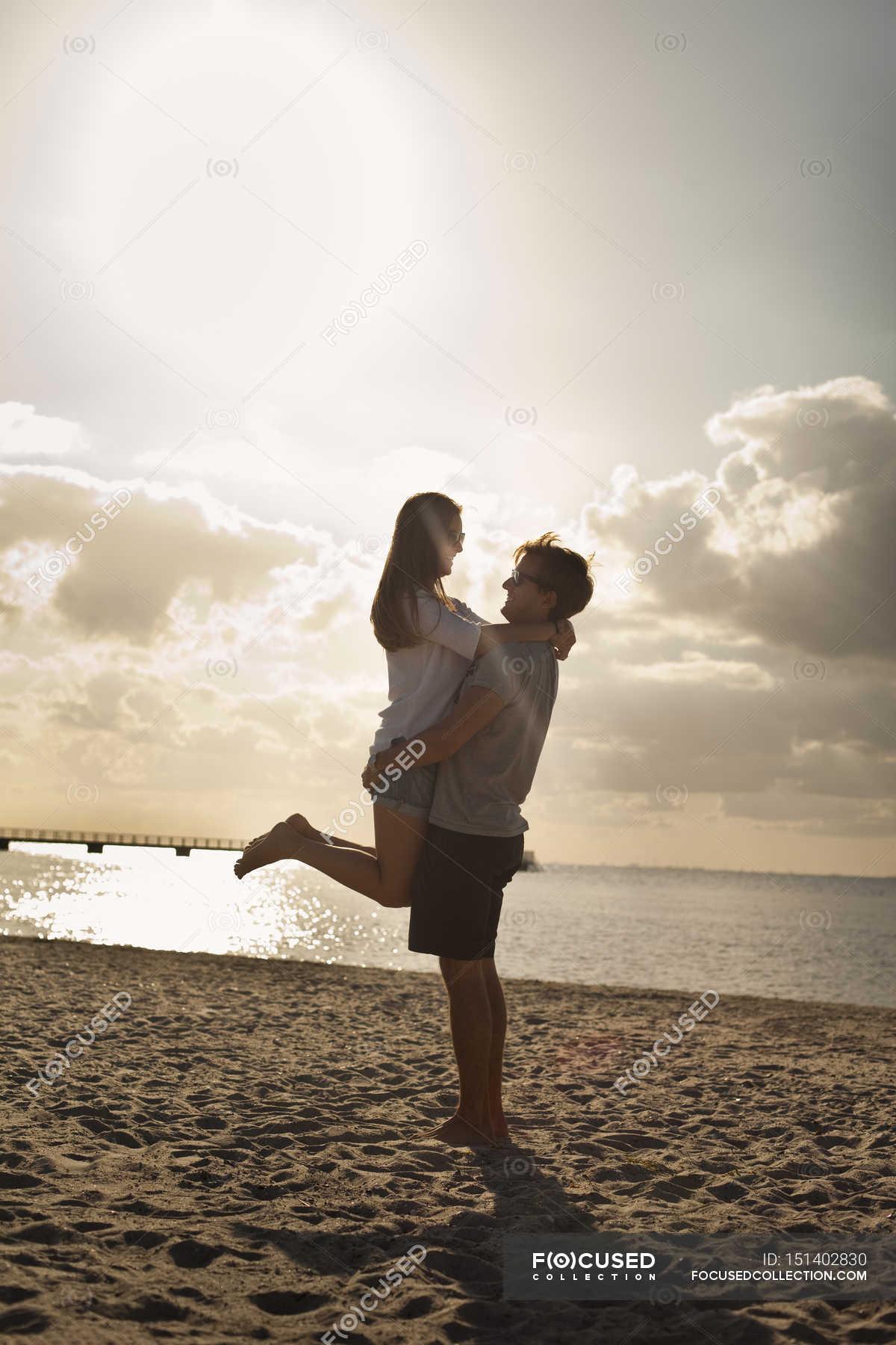 Man carrying woman at beach — Stock Photo | #151402830