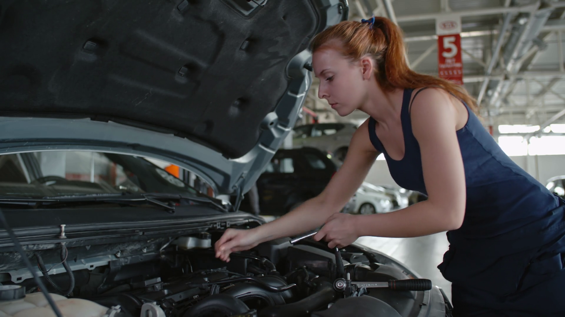 Man and woman in mechanic uniform checking details under car hood ...
