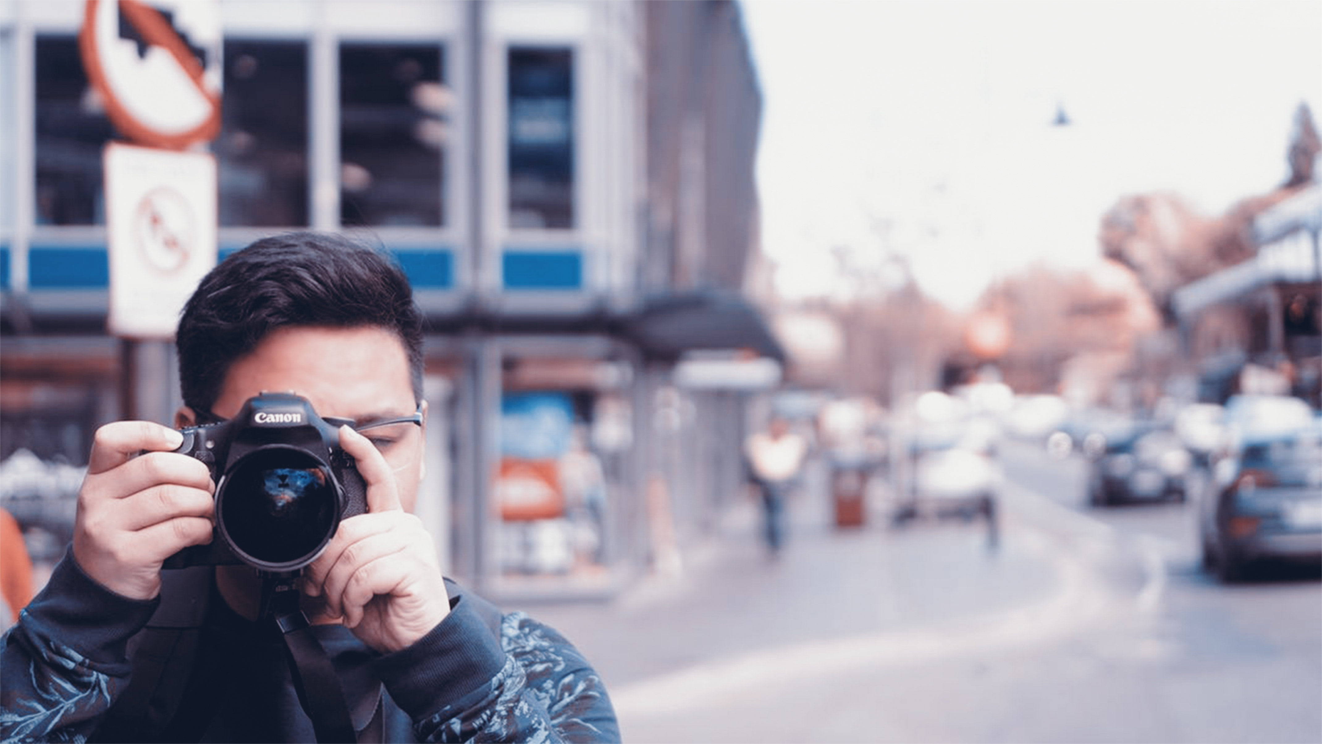 Man holding a camera on busy street photo