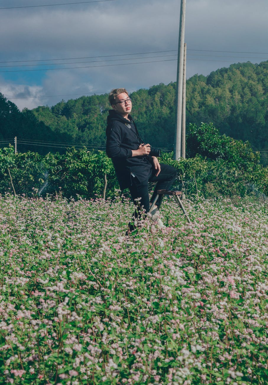 Man holding black dslr camera on green bush at daytime photo